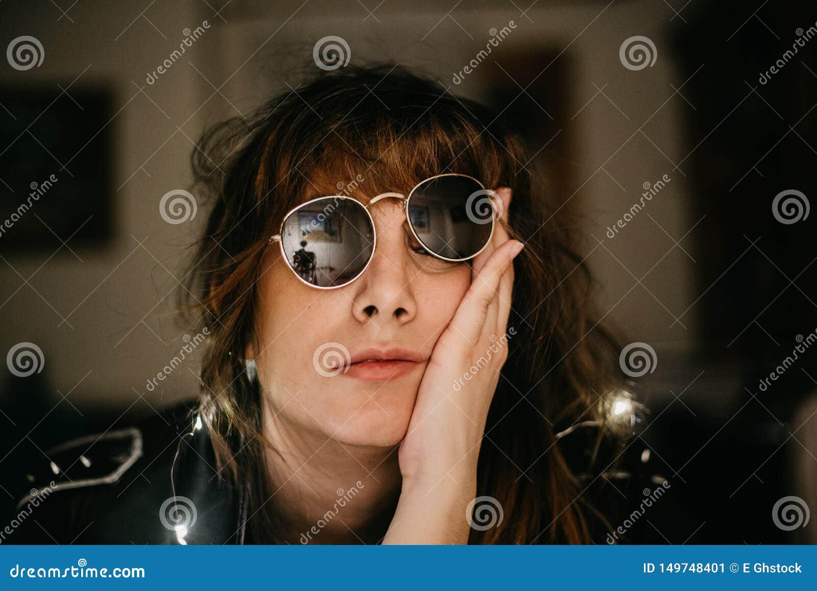 Retrato de la mujer joven aburrida con las luces y las gafas de sol llevadas