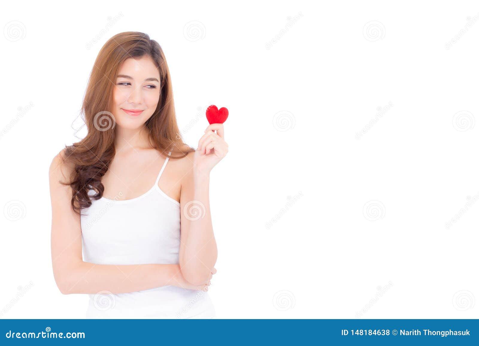 Retrato de la mujer joven asi?tica hermosa que celebra la almohada roja y la sonrisa de la forma del coraz?n aislado en el fondo