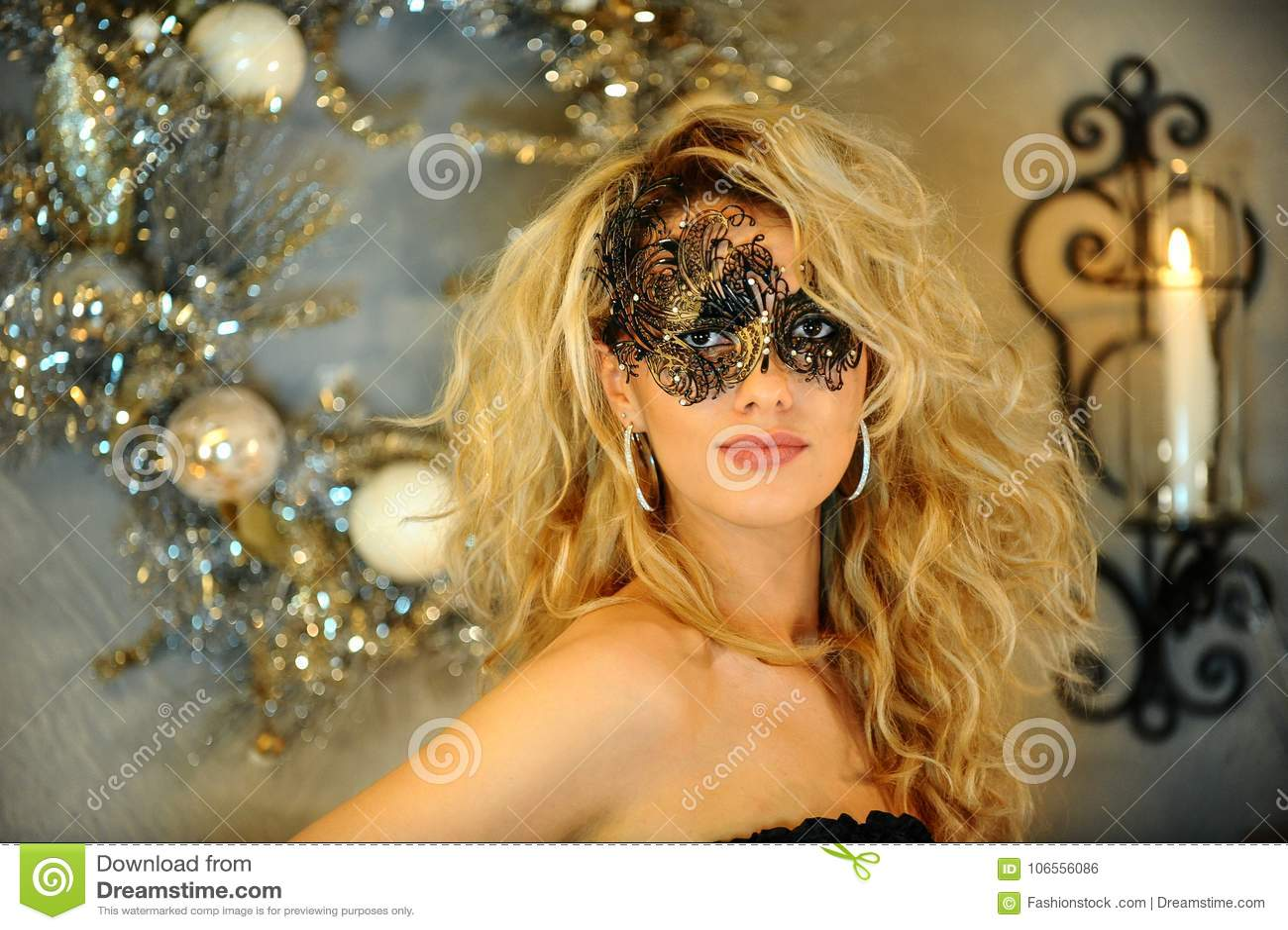Retrato de la mujer joven atractiva en ropa interior negra y la máscara veneciana