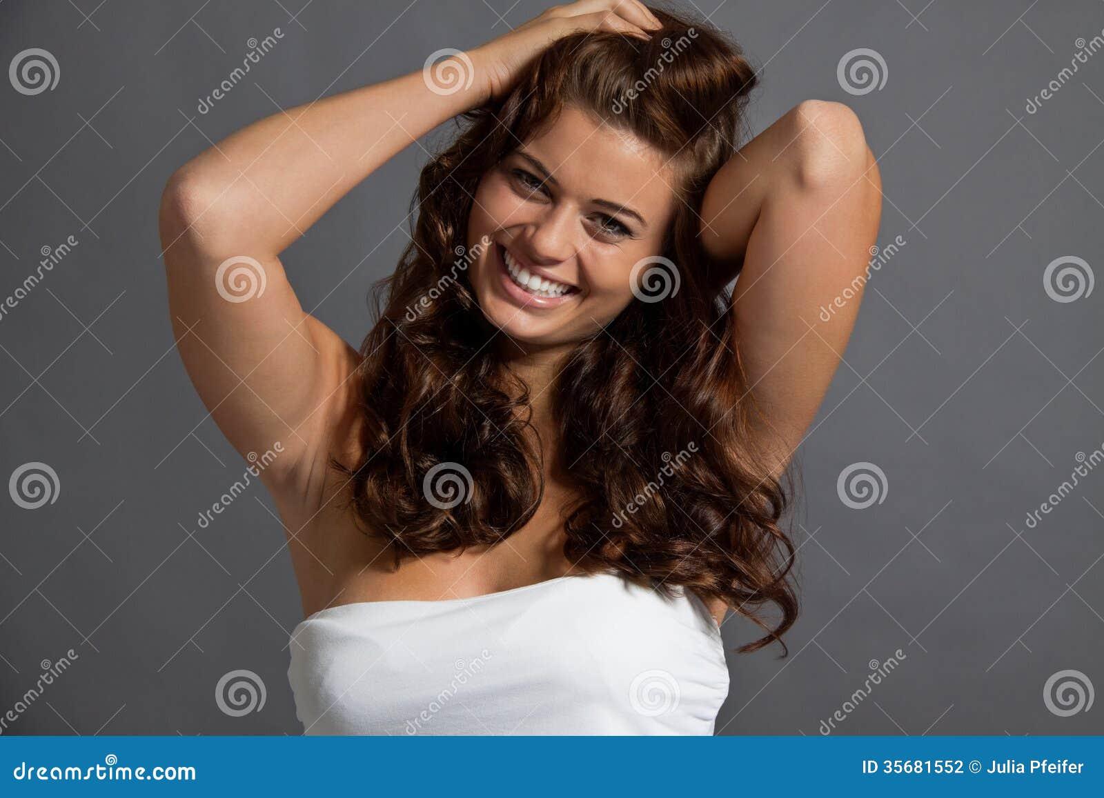 Retrato de la mujer joven con el pelo rizado marrón sano brillante