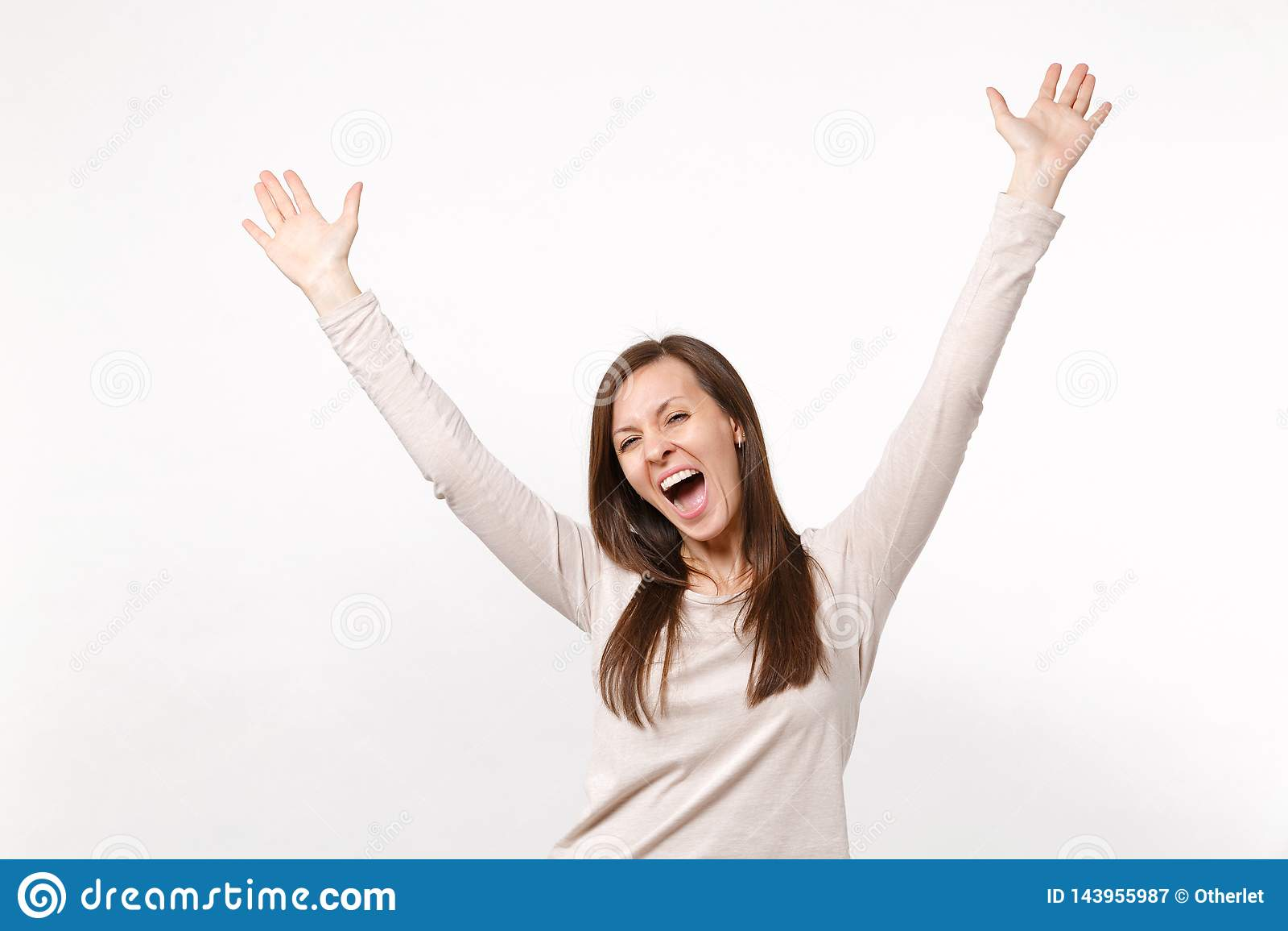 Retrato de la mujer joven de griterío extática feliz en la ropa ligera que sube, manos de extensión aisladas en la pared blanca