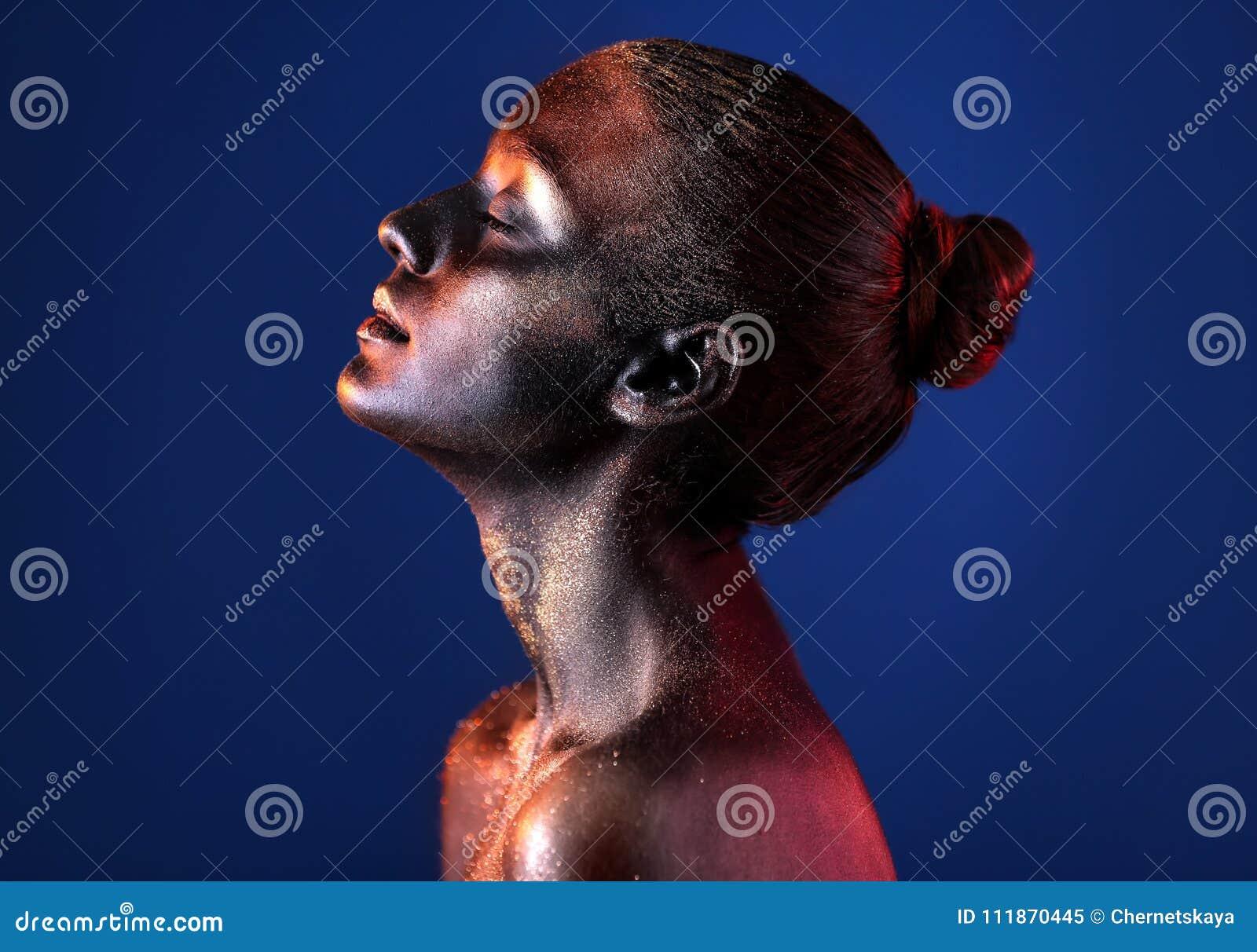 Retrato de la mujer joven hermosa con la pintura oscura