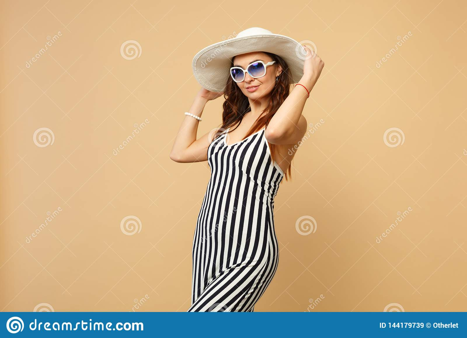 Retrato de la mujer joven imponente en el vestido, el sombrero blanco y negro y las gafas de sol rayados mirando la cámara en pas