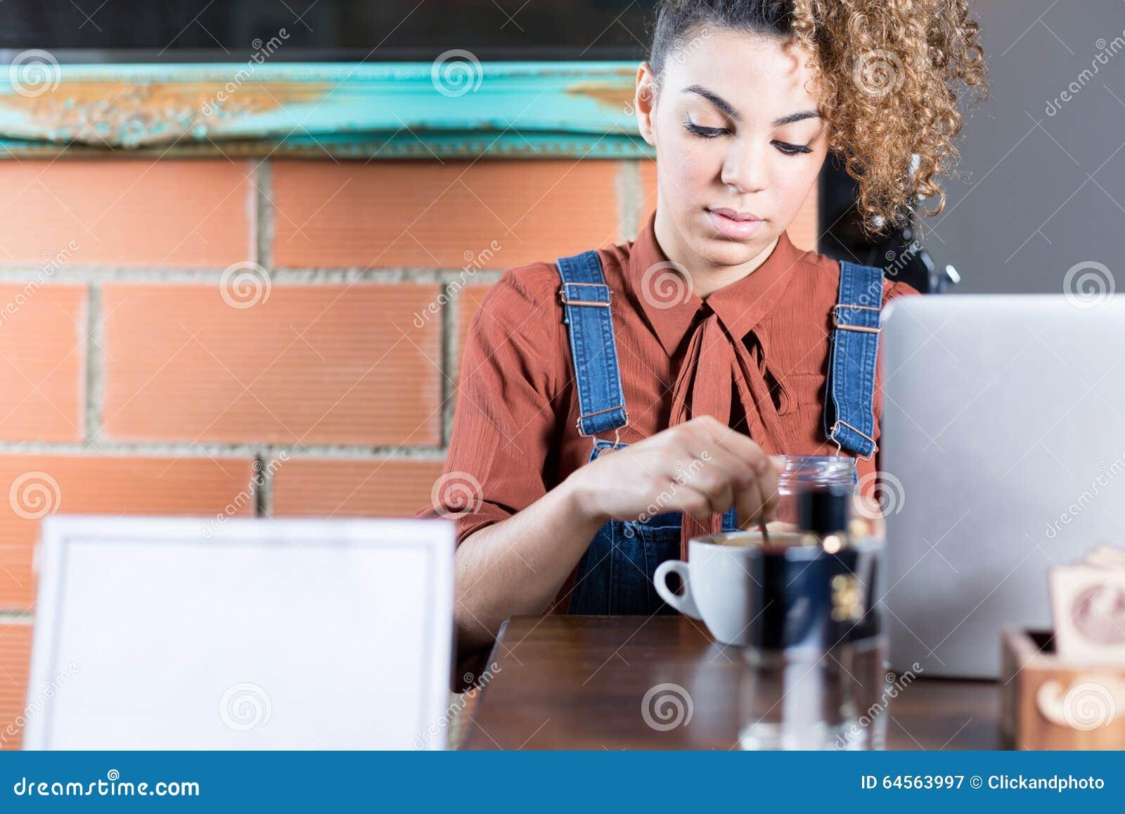 Retrato de la mujer joven que revuelve el café