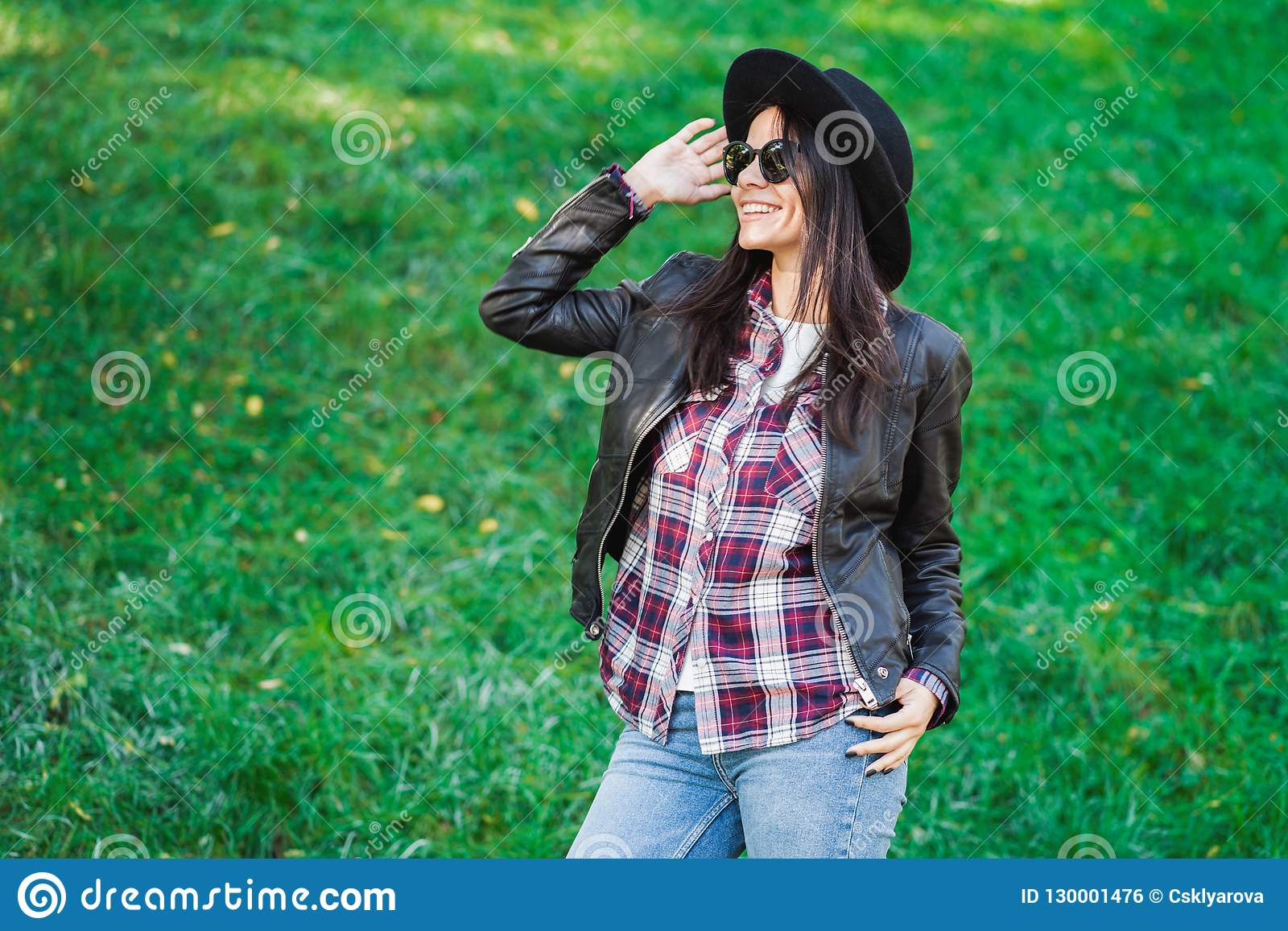 Retrato de la mujer joven de la raza mixta feliz en sombrero Muchacha hispánica del inconformista en el parque Camisa de tela esc