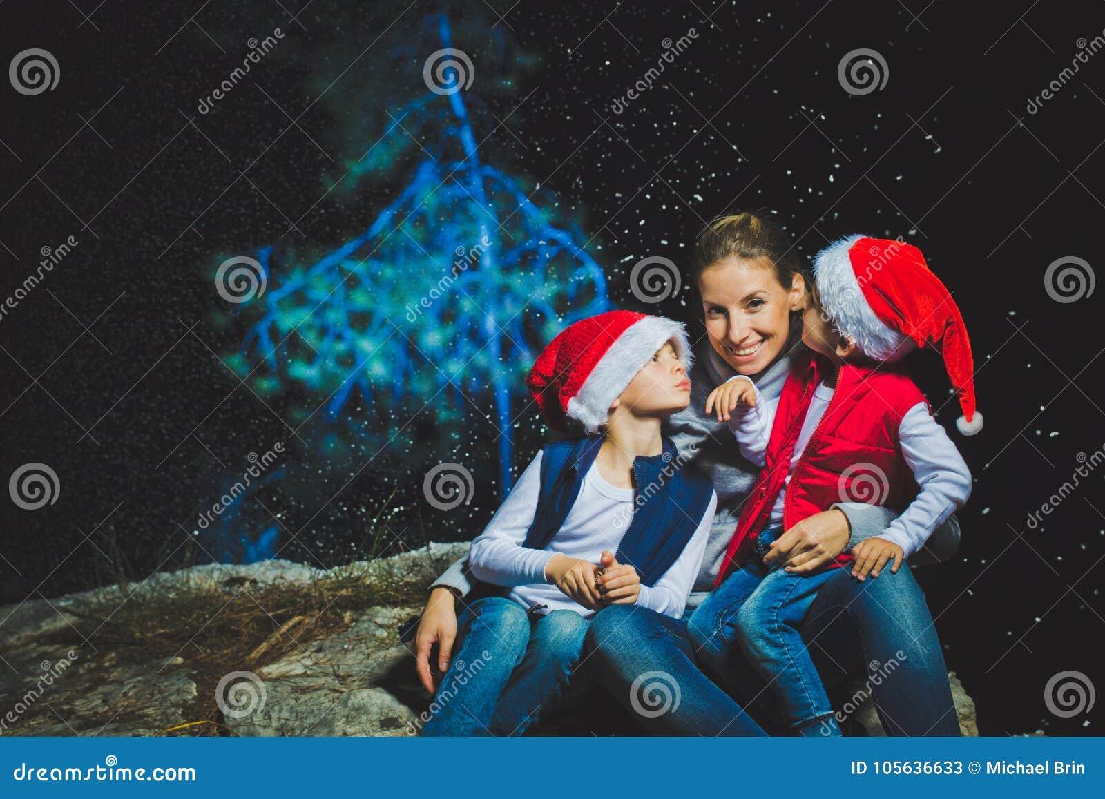 Retrato de la mujer joven sonriente feliz y de kidboy lindo con las bengalas que celebran la Navidad al aire libre con el árbol a