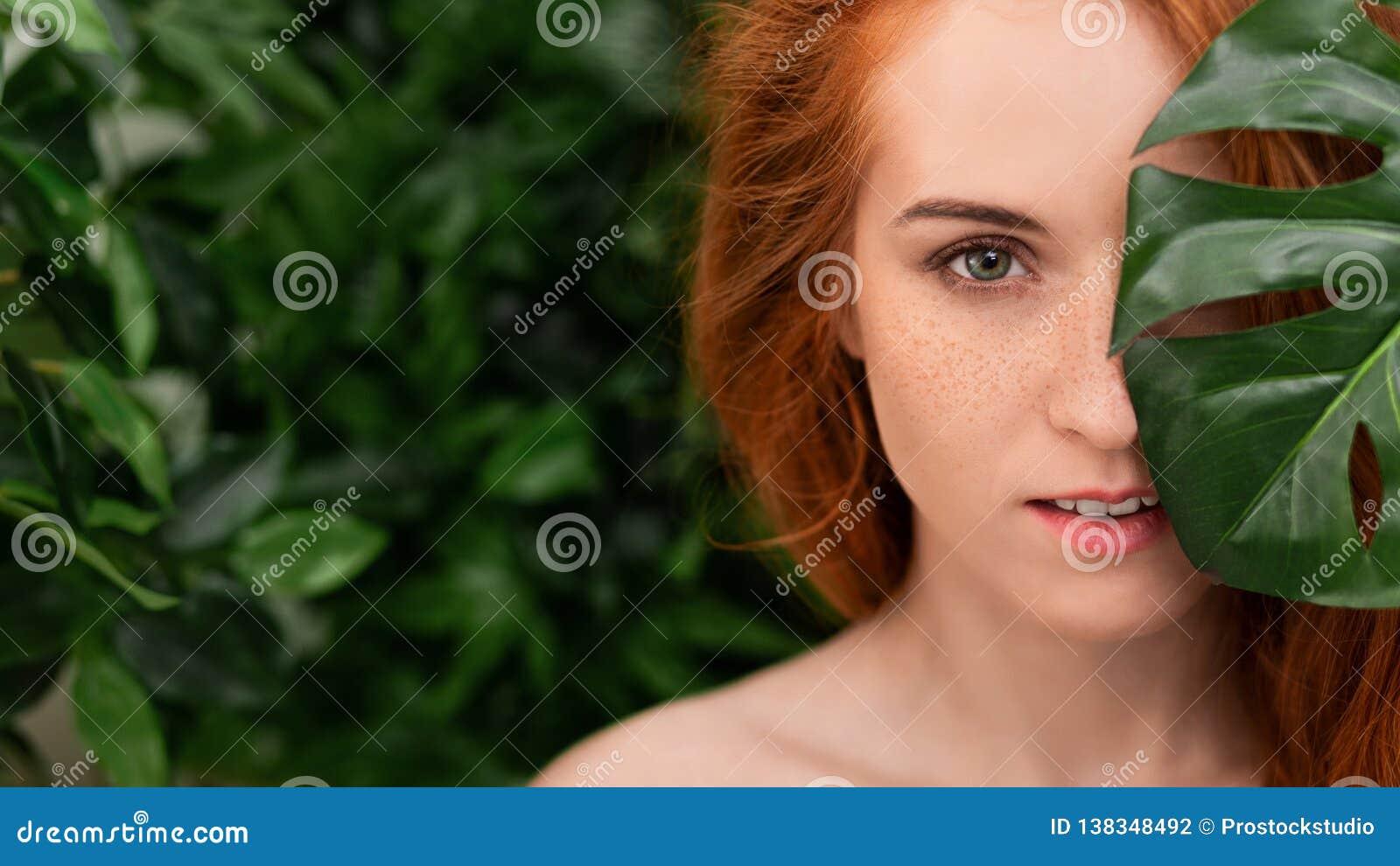 Retrato de la mujer joven y hermosa en hojas tropicales