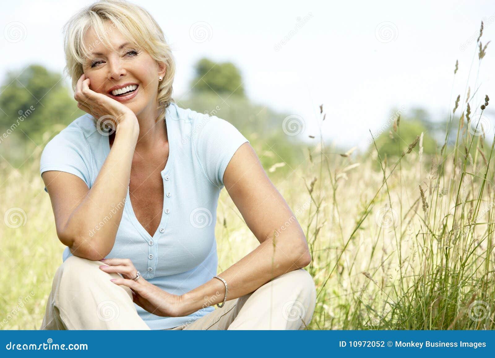 Retrato de la mujer madura que se sienta en campo
