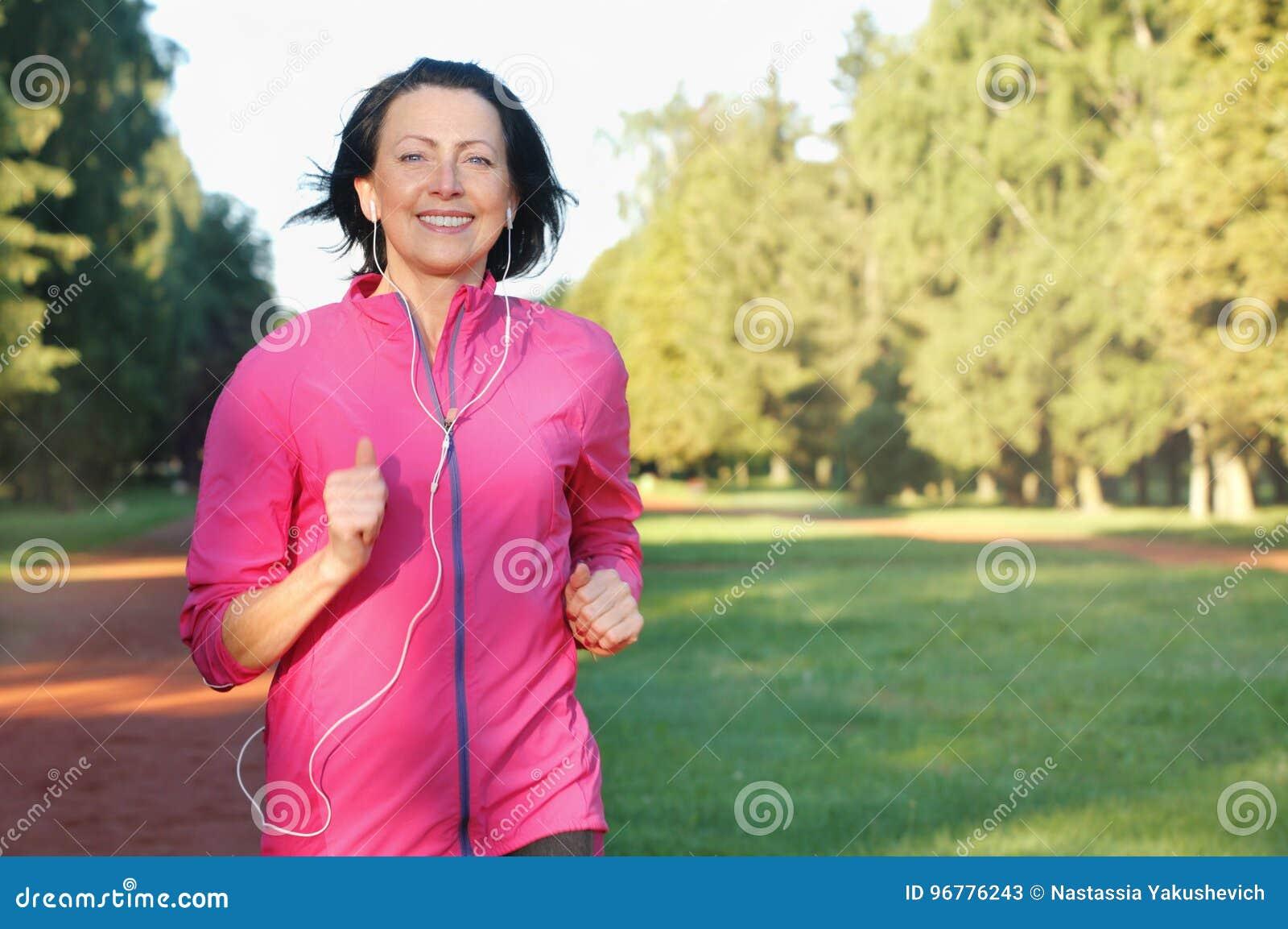 Retrato de la mujer mayor que corre con los auriculares en el parque