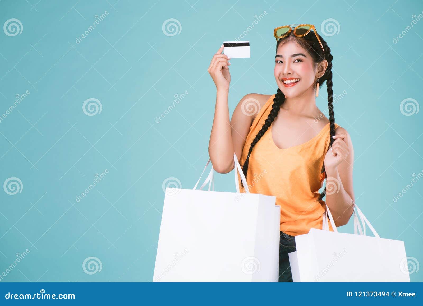 Retrato de la mujer morena joven alegre que sostiene la tarjeta y los panieres de crédito