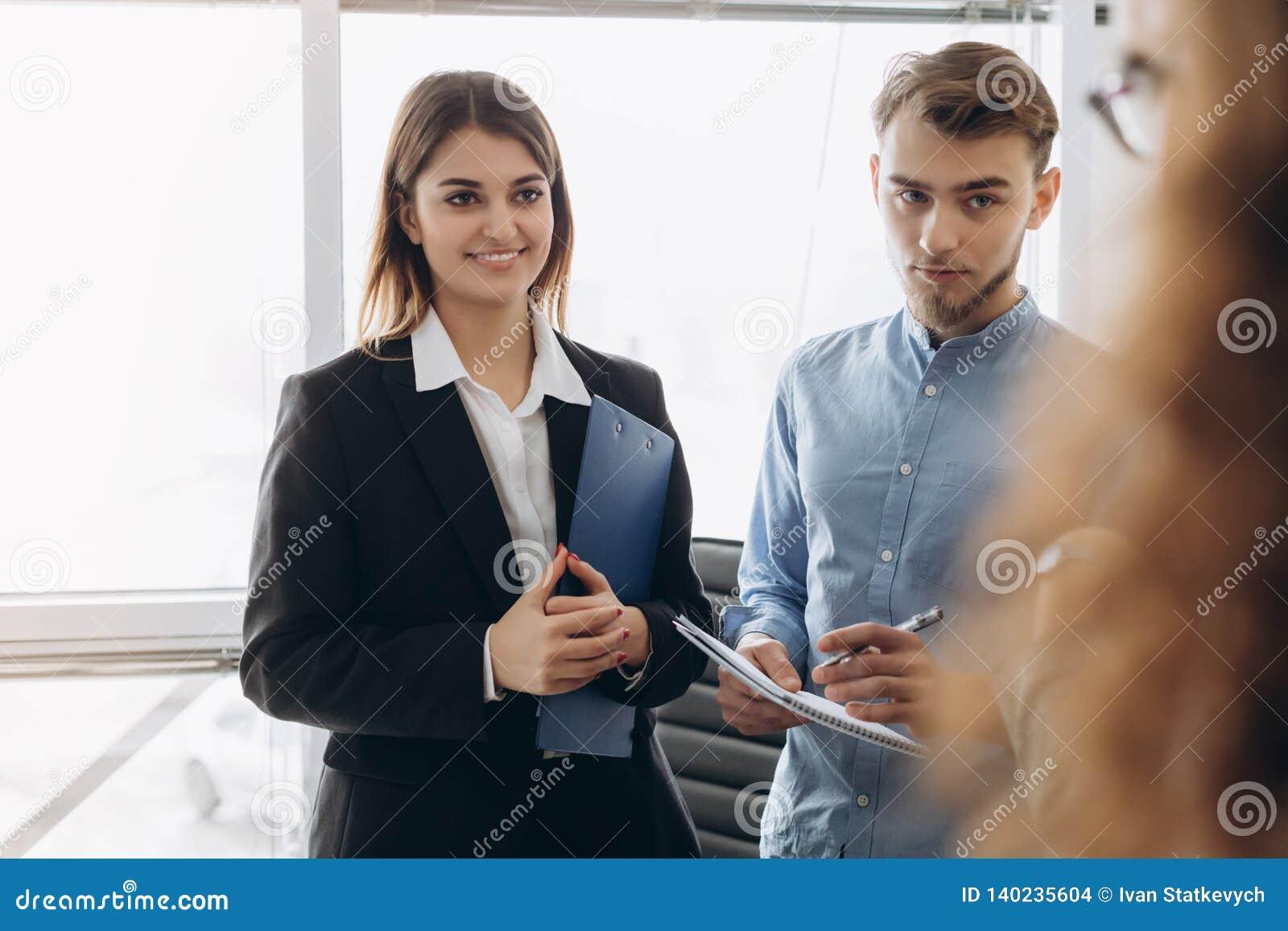 Retrato de la mujer de negocios hermosa joven en la oficina que habla con los trabajadores