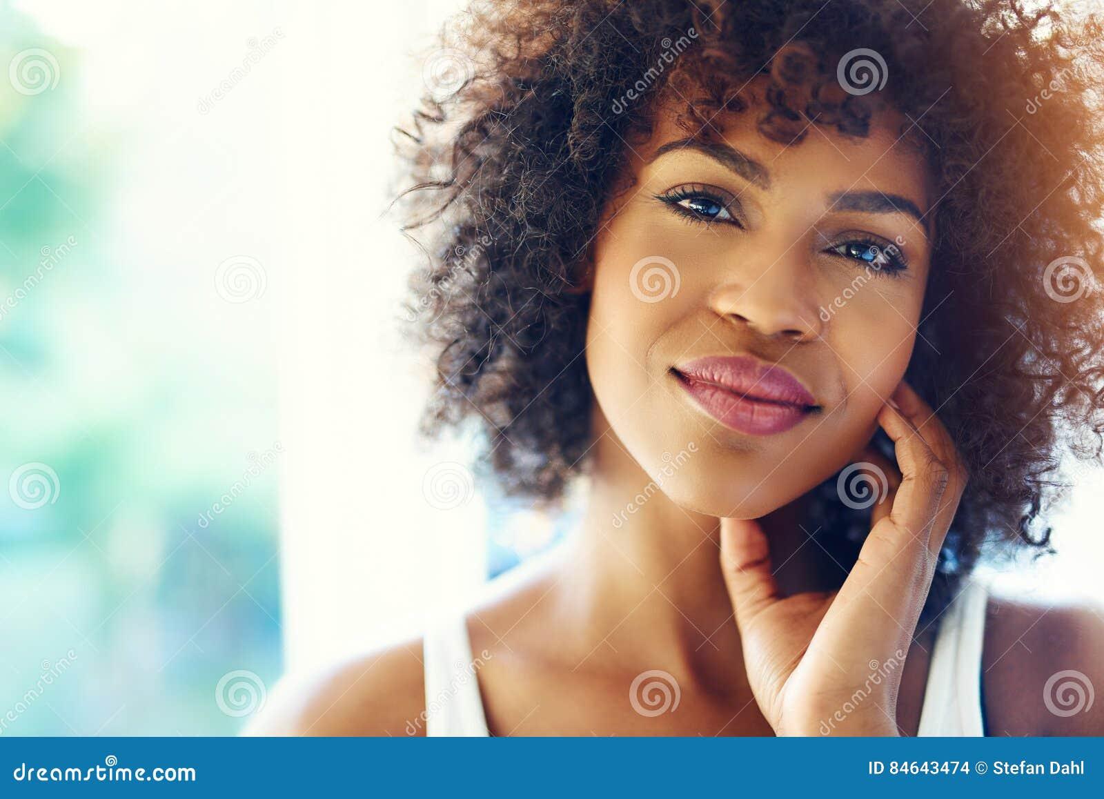 Retrato de la mujer negra joven sonriente en sol