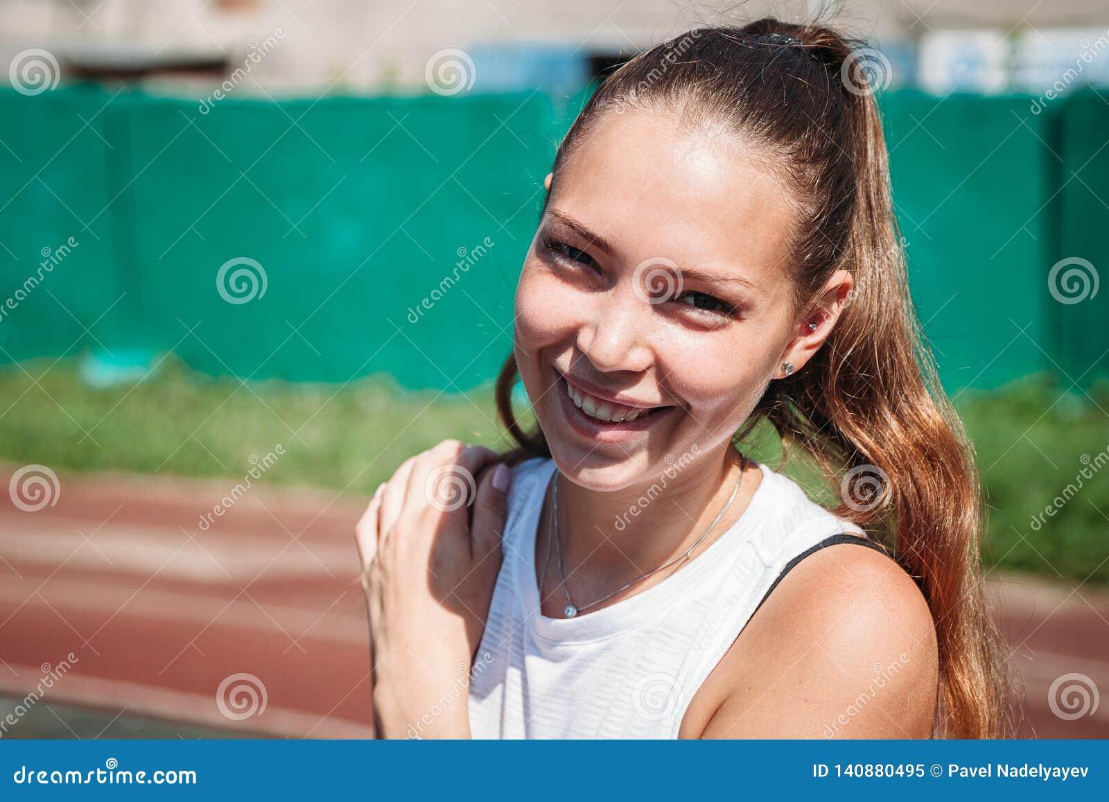 Retrato de la mujer rubia joven atlética hermosa que sonríe en la cámara
