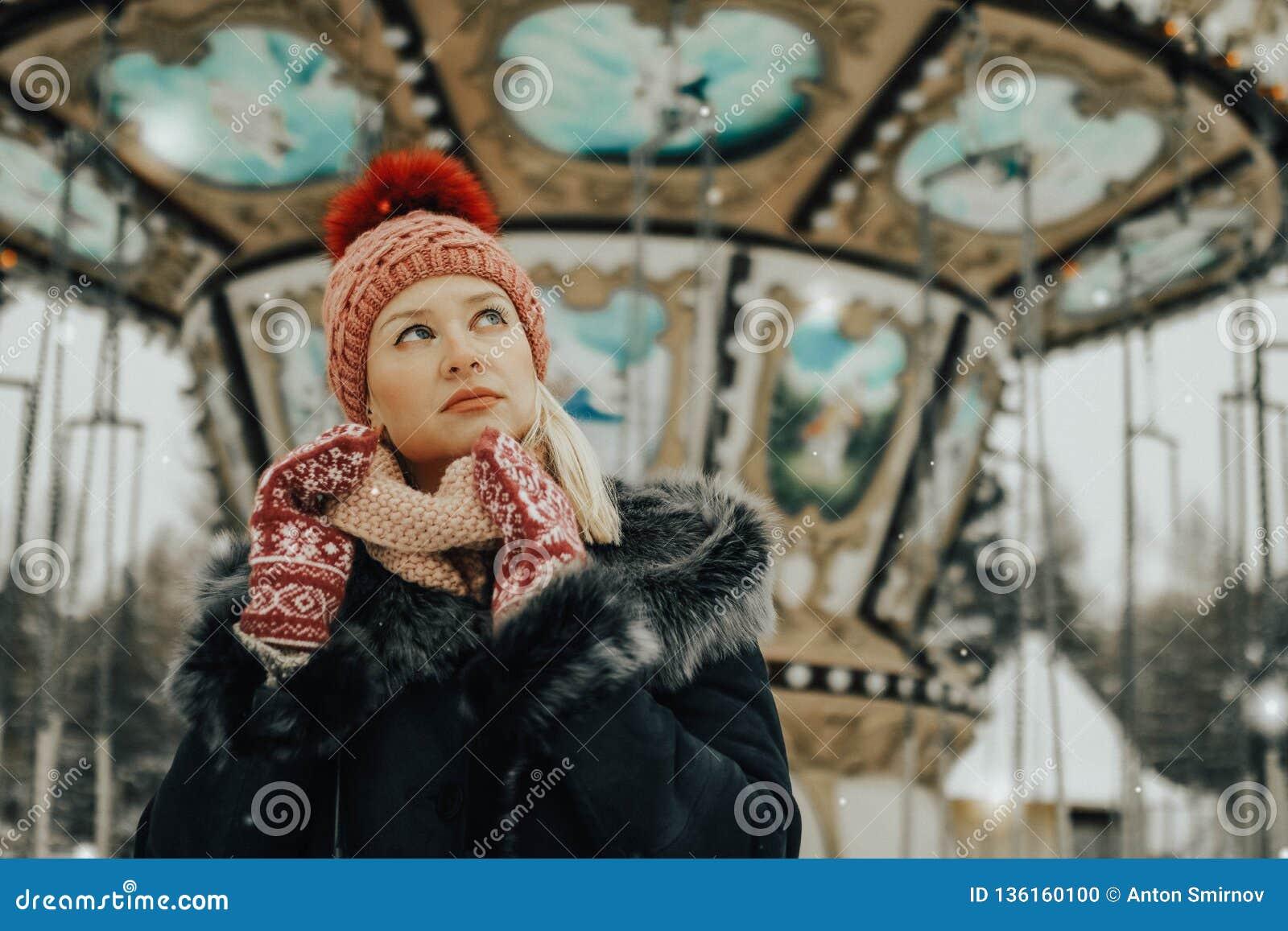Retrato de la mujer rubia joven en ropa del invierno Casquillo y manoplas rojos El caminar en el parque