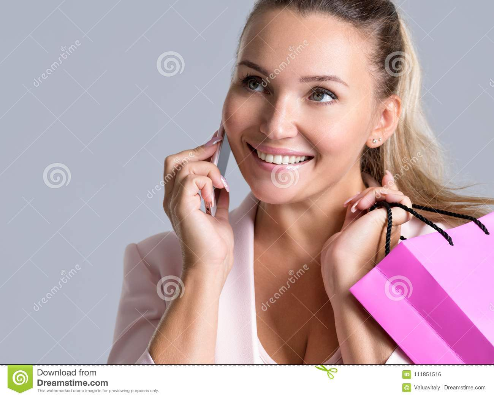 Retrato de la mujer sonriente feliz con el bolso rosado que habla en la mañana