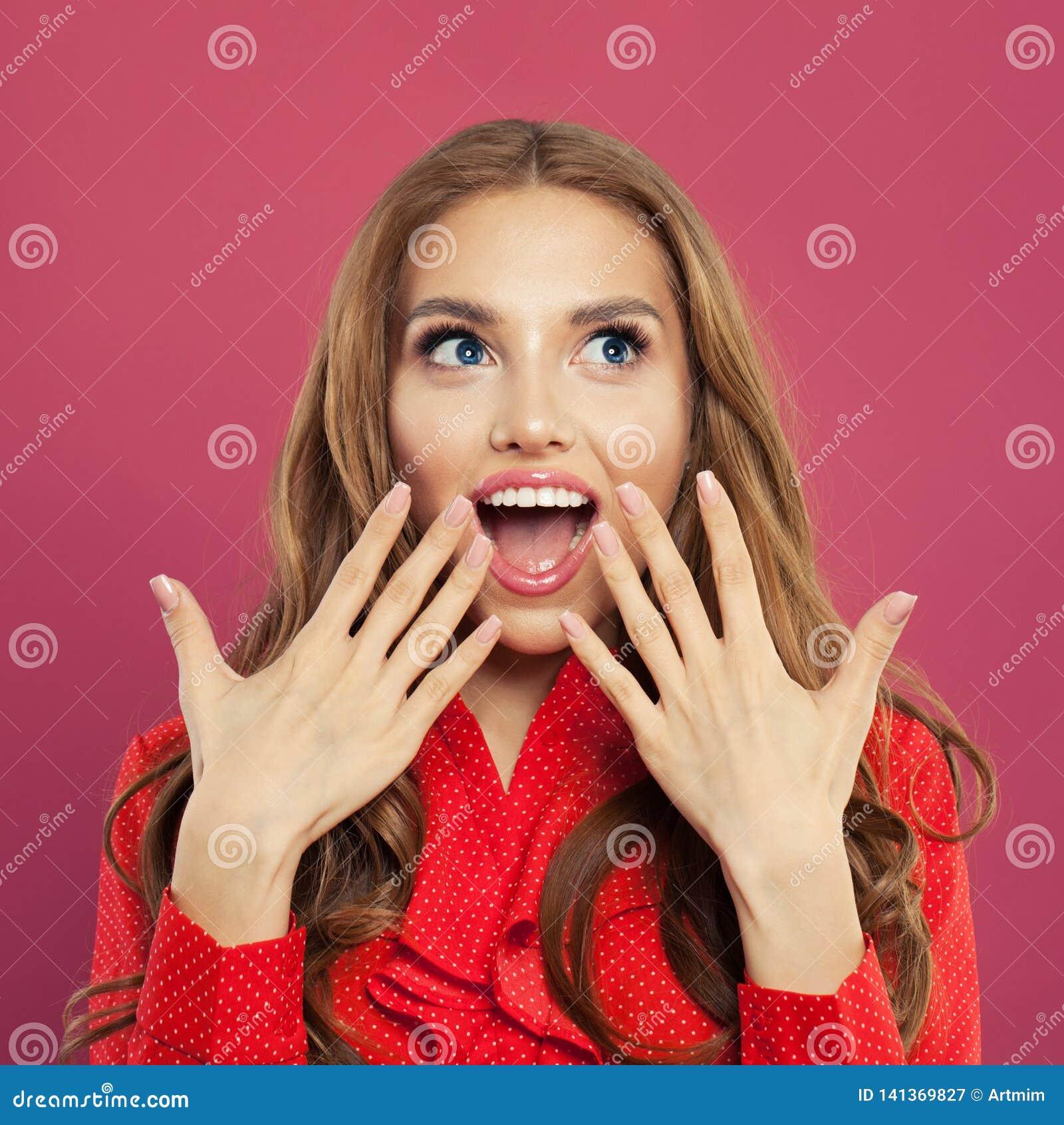 Retrato de la mujer sorprendida feliz en fondo rosado brillante colorido Tiro del estudio de la muchacha rizada bastante emociona