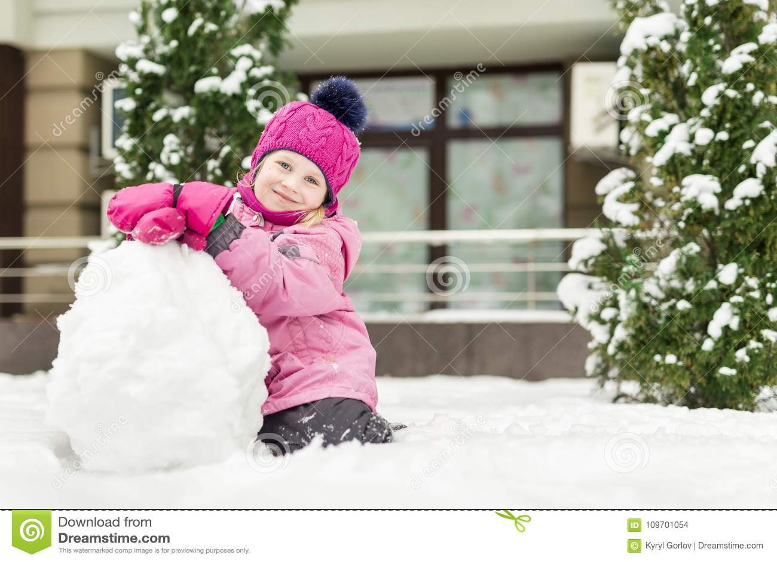 Retrato de la niña linda que hace smowman en el día de invierno brillante Niño adorable que juega con nieve al aire libre diverti
