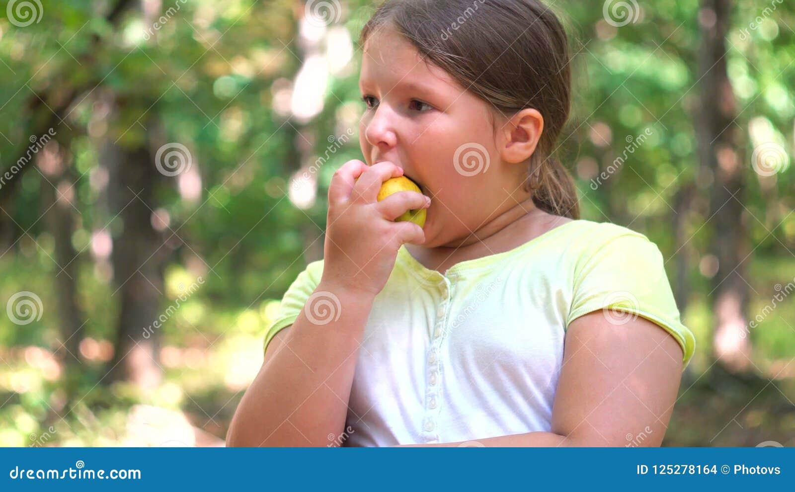 Retrato de la niña que come la manzana al aire libre de la manzana al día de verano
