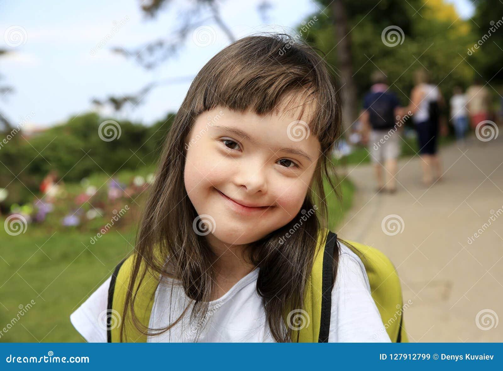 Retrato de la niña que sonríe en la ciudad
