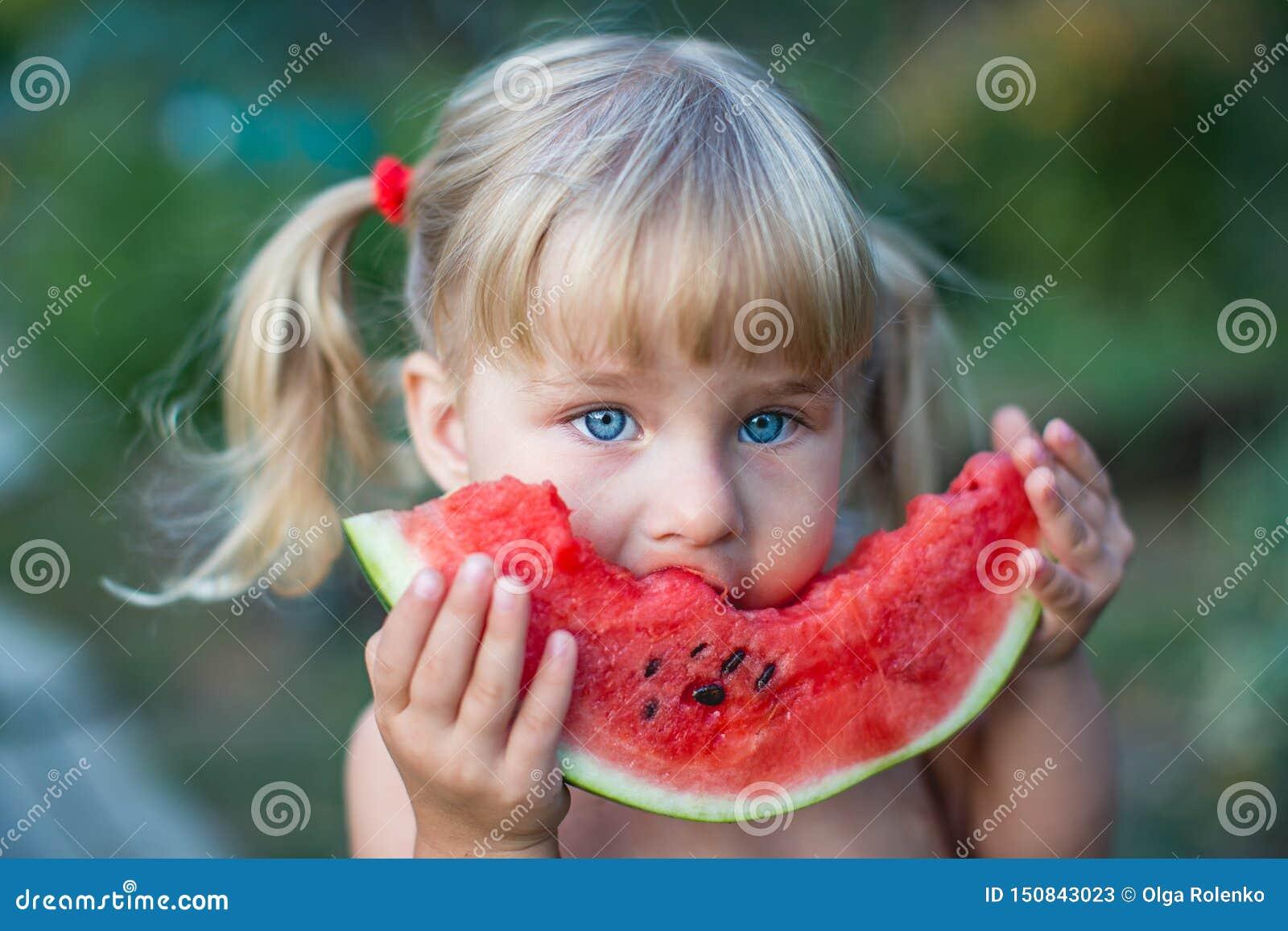 Retrato de la niña rubia hermosa con dos colas de caballo que come la sandía