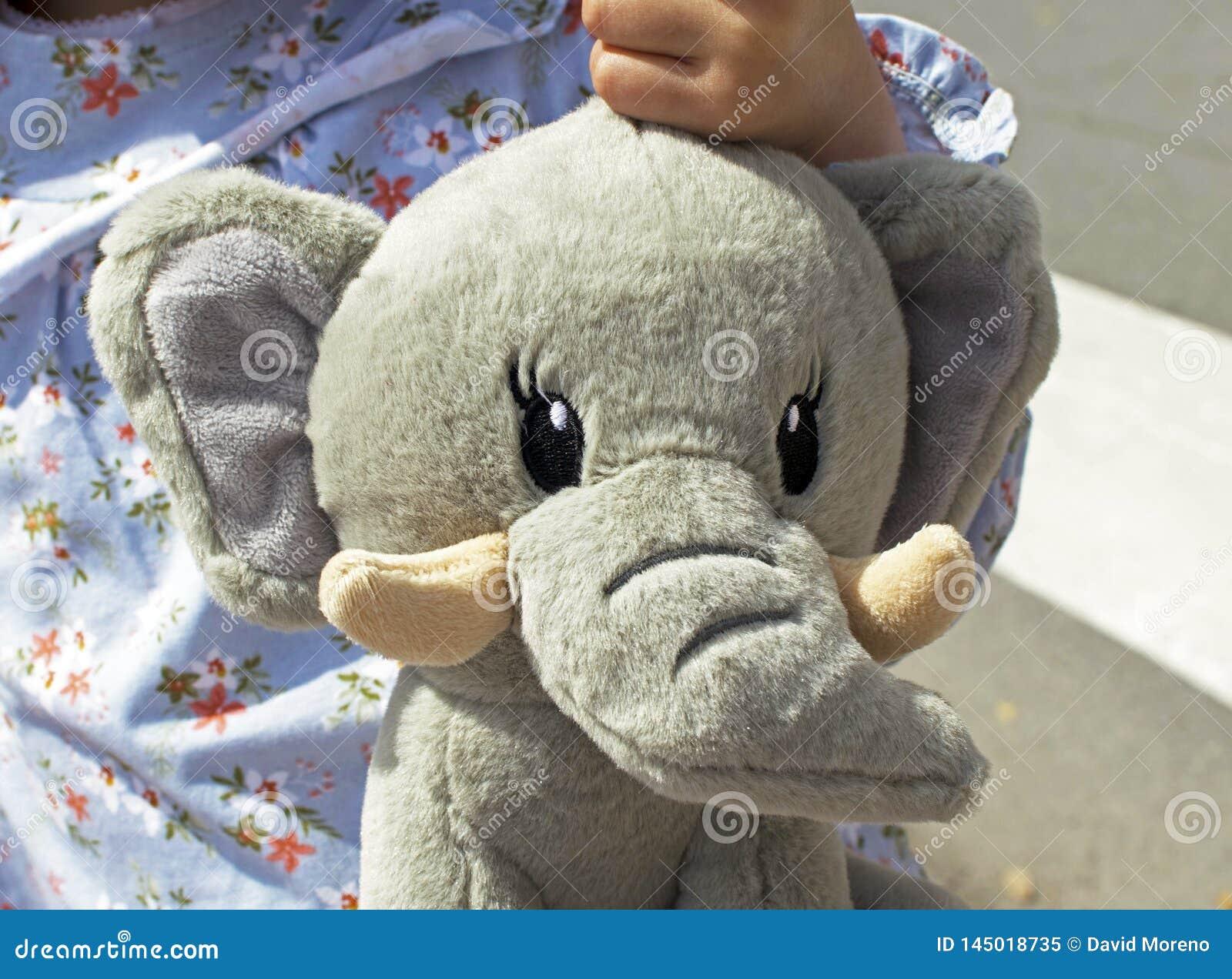Retrato de la niña sonriente con un elefante del peluche