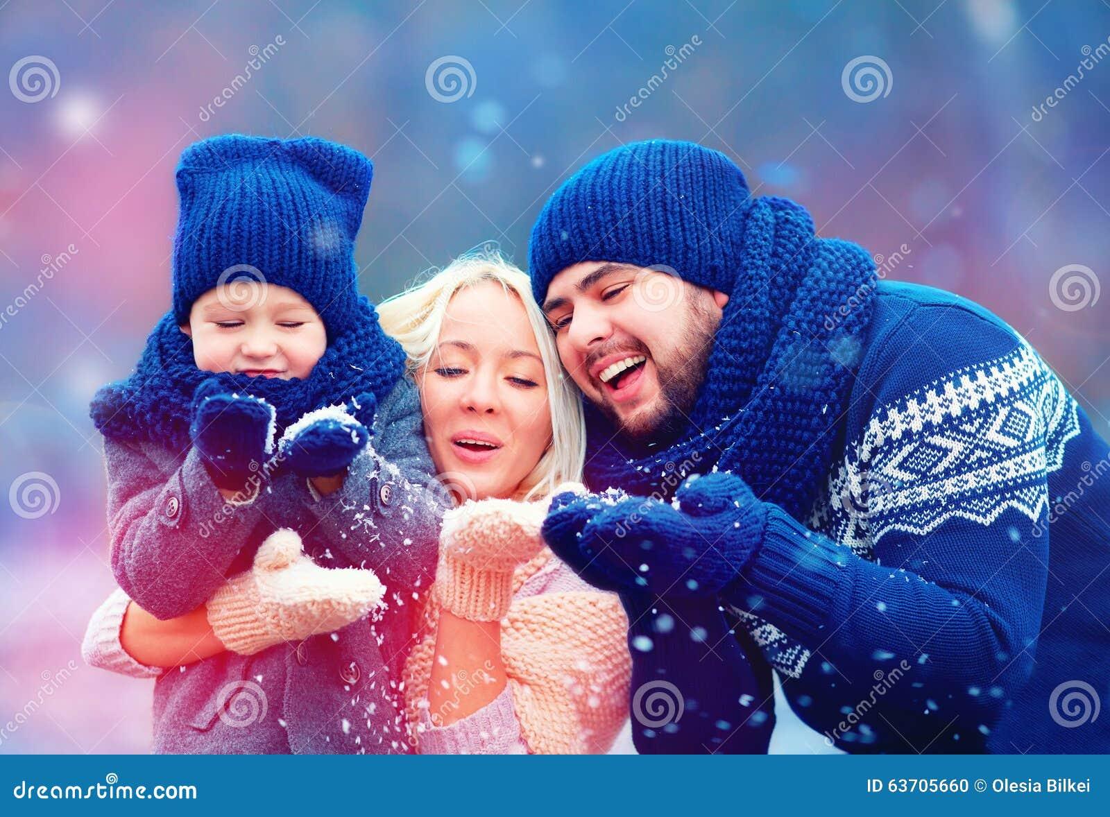 Retrato de la nieve del invierno de la familia que sopla feliz