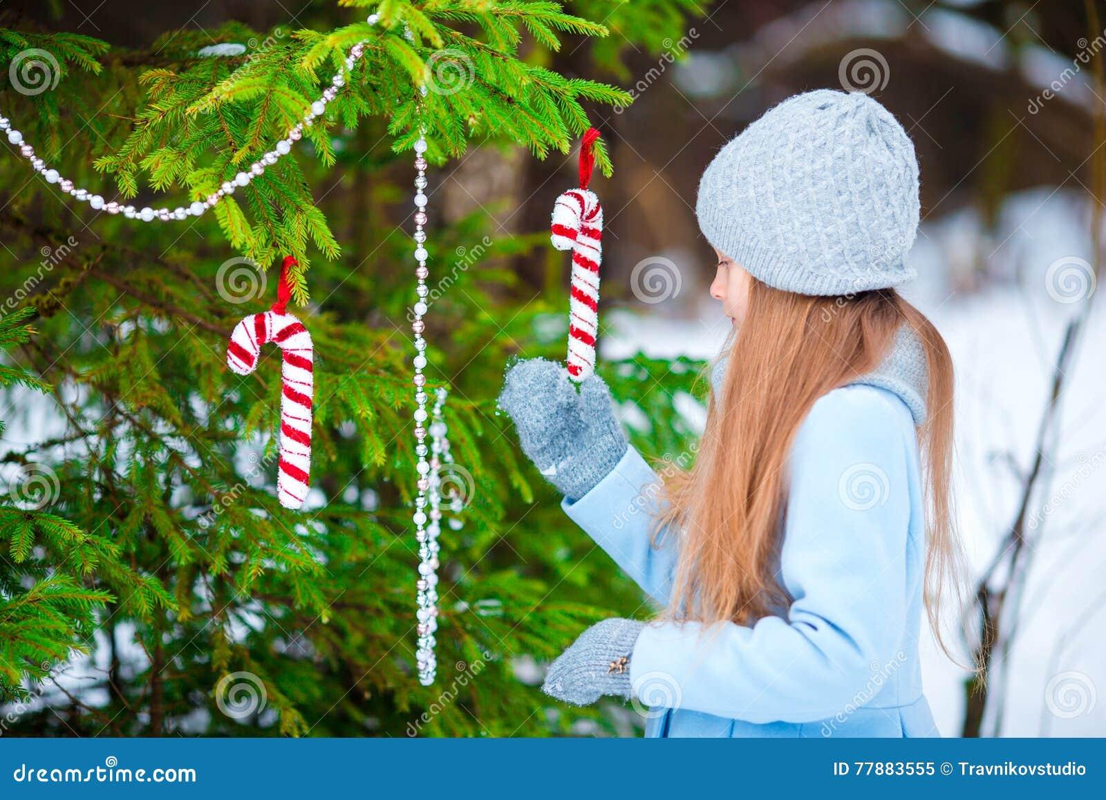 Retrato De La Pequeña Muchacha Adorable En Capa Azul Y Las Manoplas Que Se Colocan Cerca Del árbol De Navidad Adornado En Inviern Foto de archivo