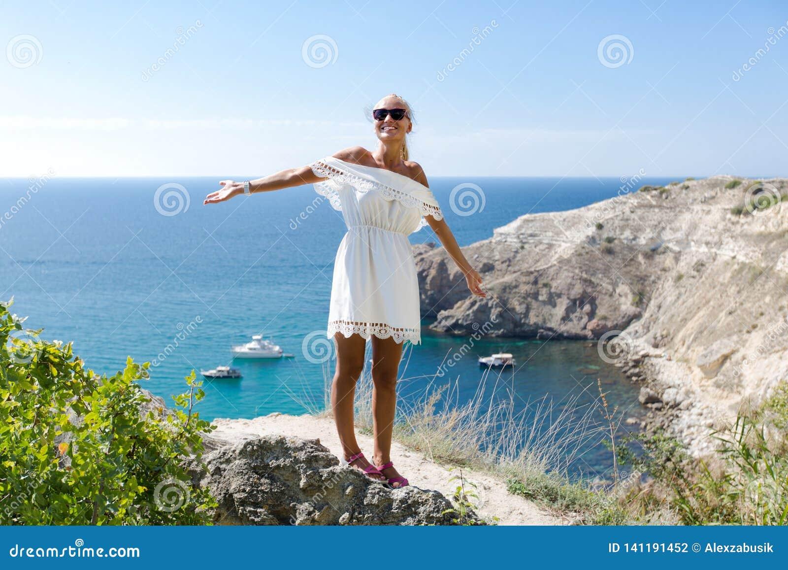 Retrato de la persona femenina atractiva en los sundress blancos contra paisaje marino