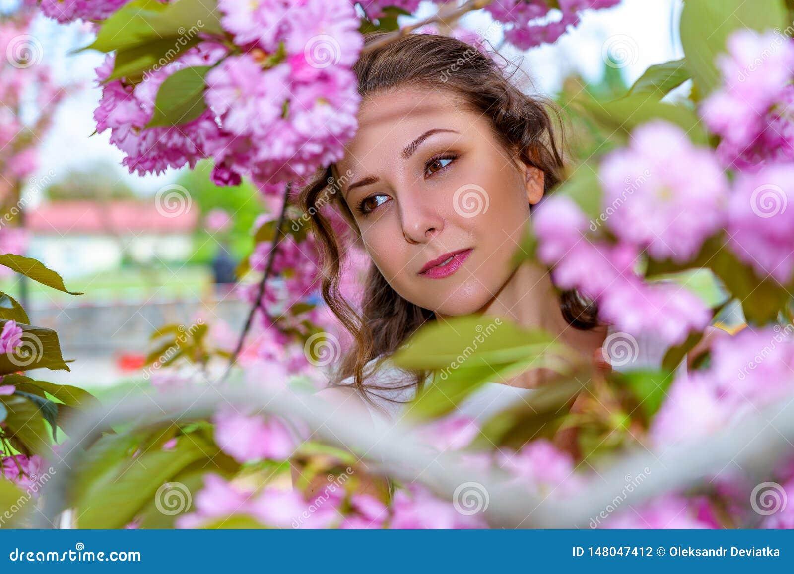 Retrato de la señora joven hermosa en el flor de flores rosadas