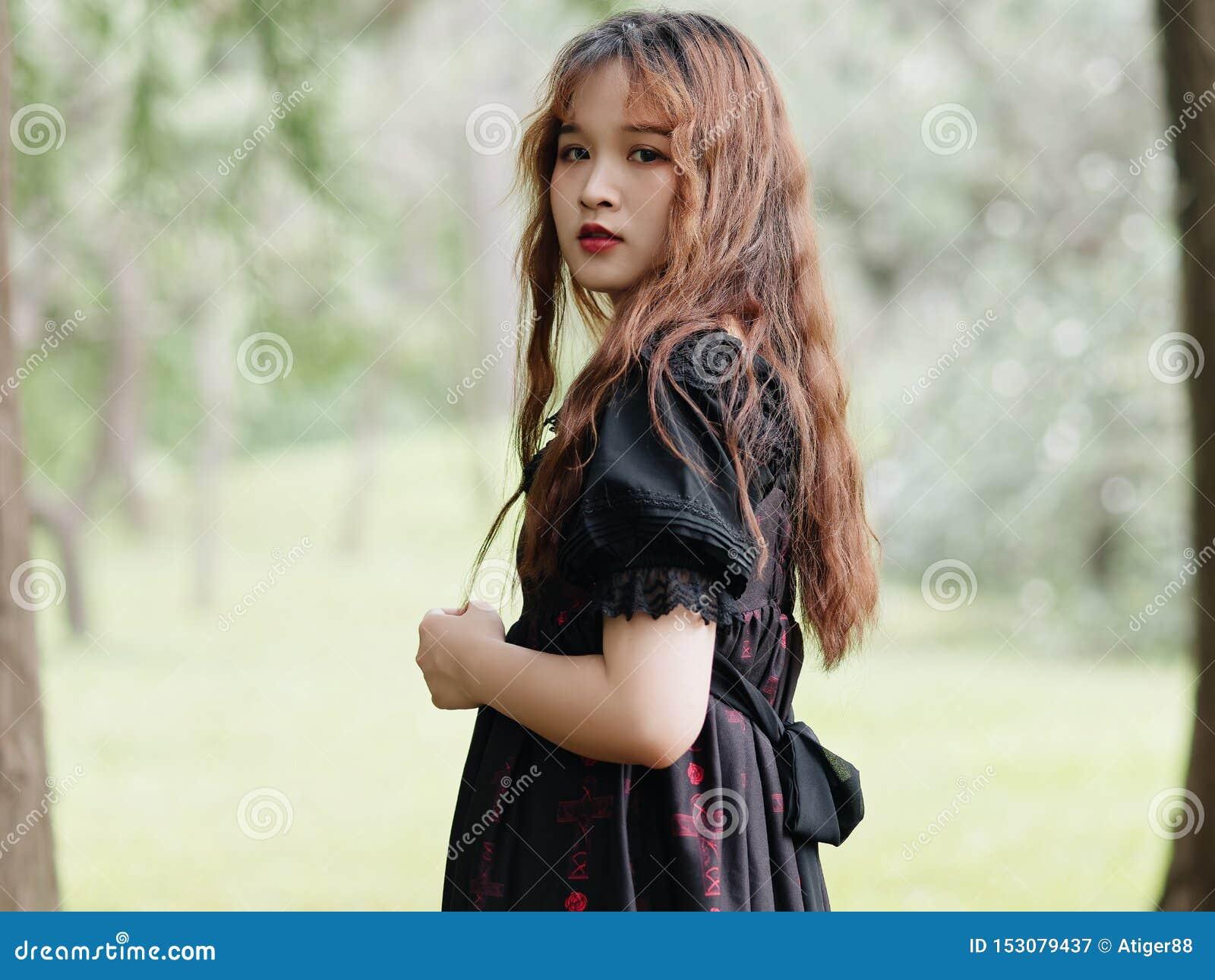 Retrato de la situación asiática hermosa de la mujer en el bosque del verano, muchacha china en el vestido negro del vintage que