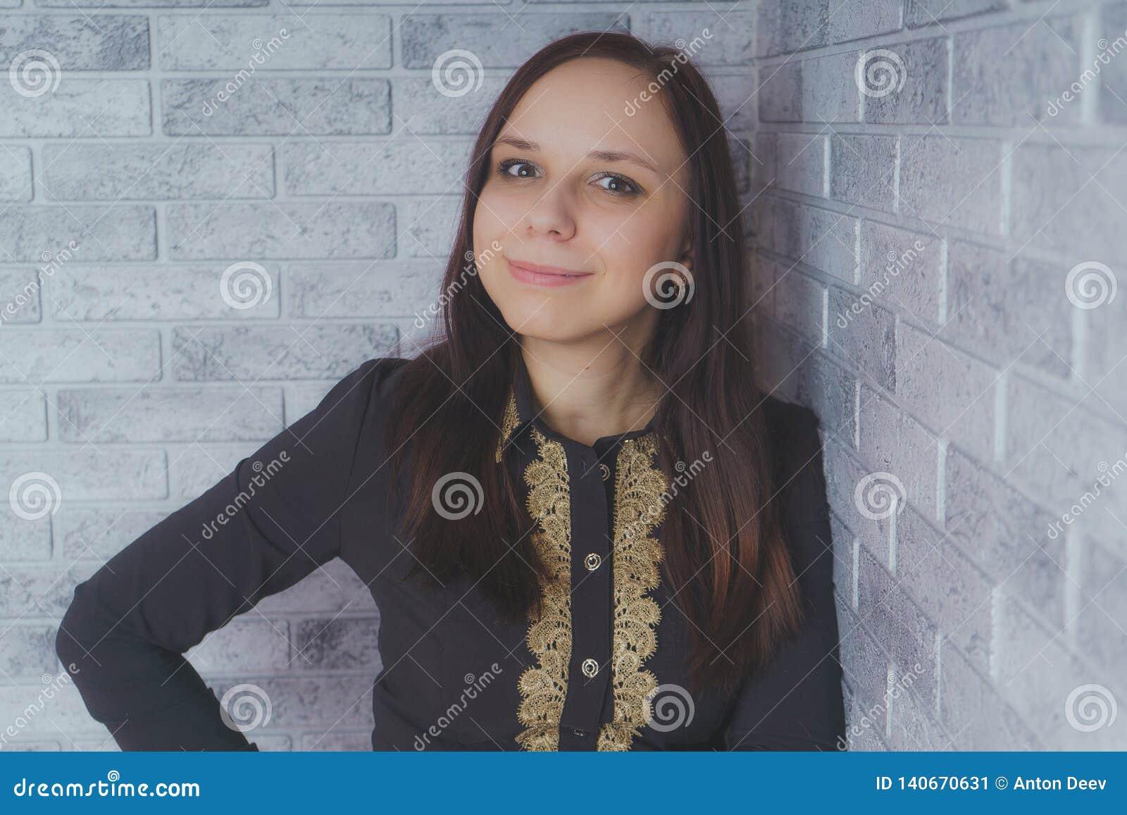 Retrato de la situación hermosa de la felicidad de la mujer joven en fondo gris del ladrillo de la pared del grunge de la textura