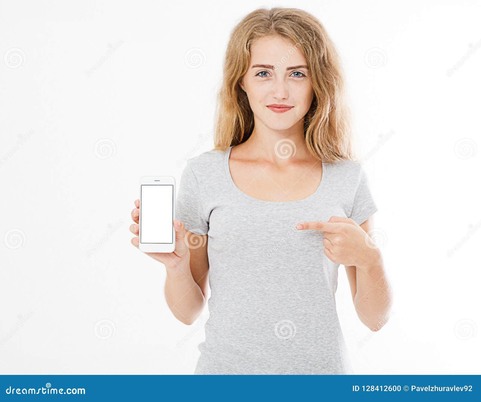 Retrato de la sonrisa atractivo, bonito, mujer, muchacha en el teléfono móvil del control de la camiseta, el señalar del móvil de