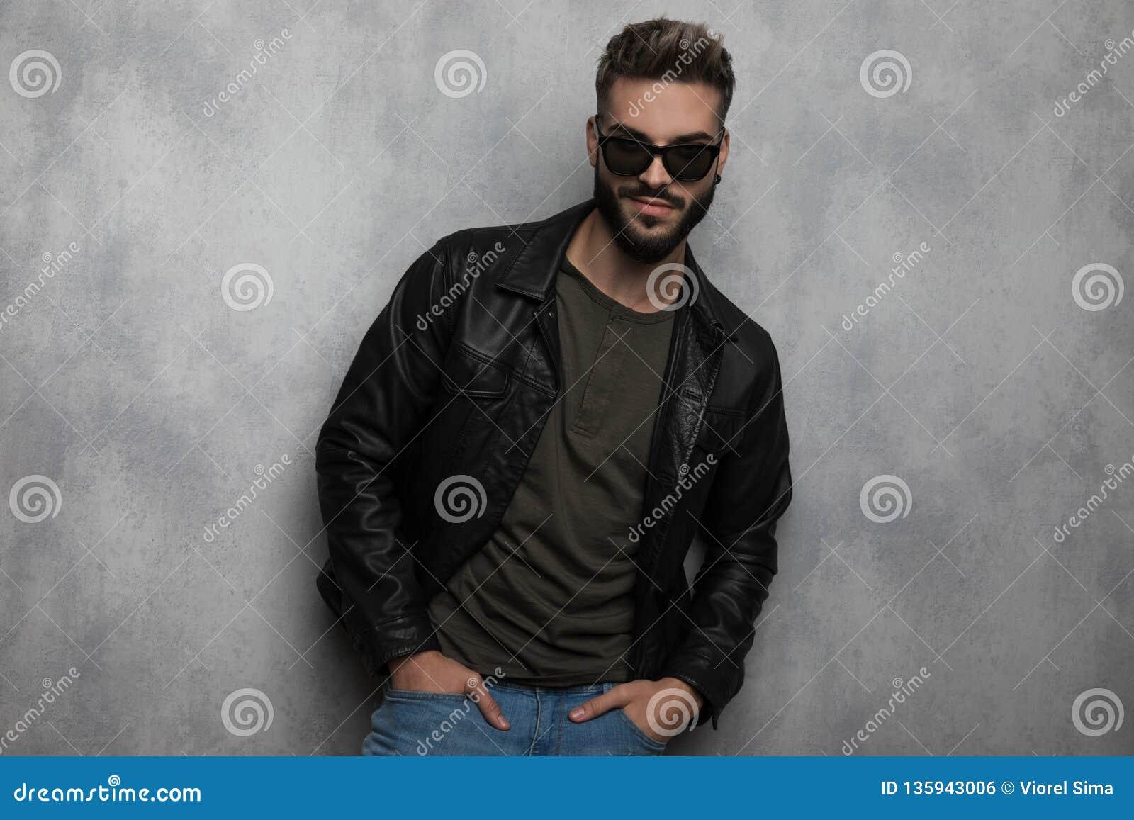 Retrato de la sonrisa de la chaqueta de cuero y de las gafas de sol del hombre que lleva relajado