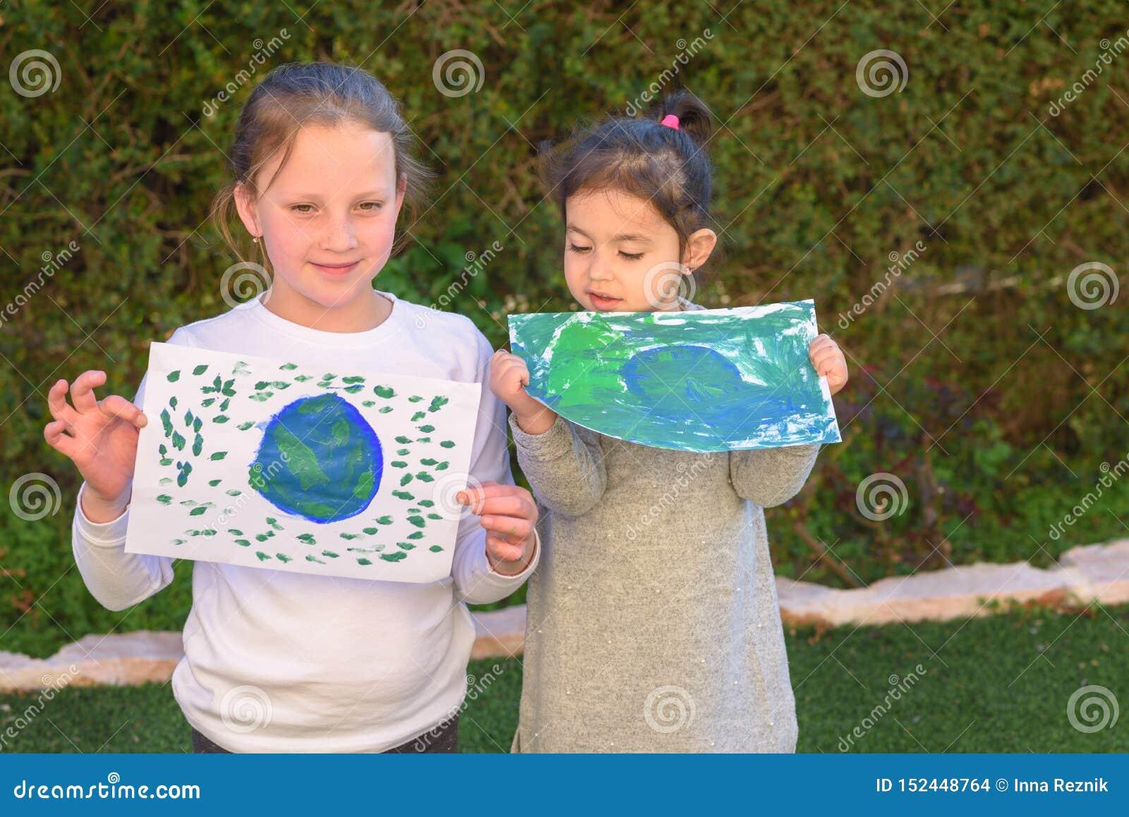 Retrato de las dos niñas lindas que sostienen el globo de dibujo de la tierra Imagen del paintig de los niños de la tierra que se