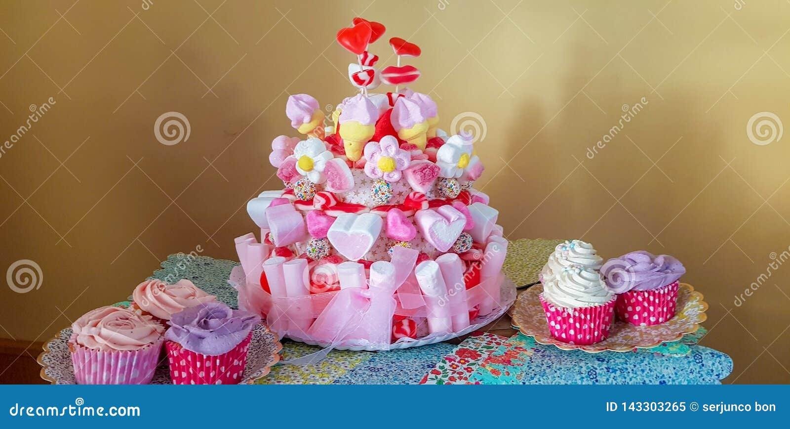 Retrato de las fuentes de la fiesta de cumpleaños esquina dulce con la torta, los polos, las galletas y el caramelo