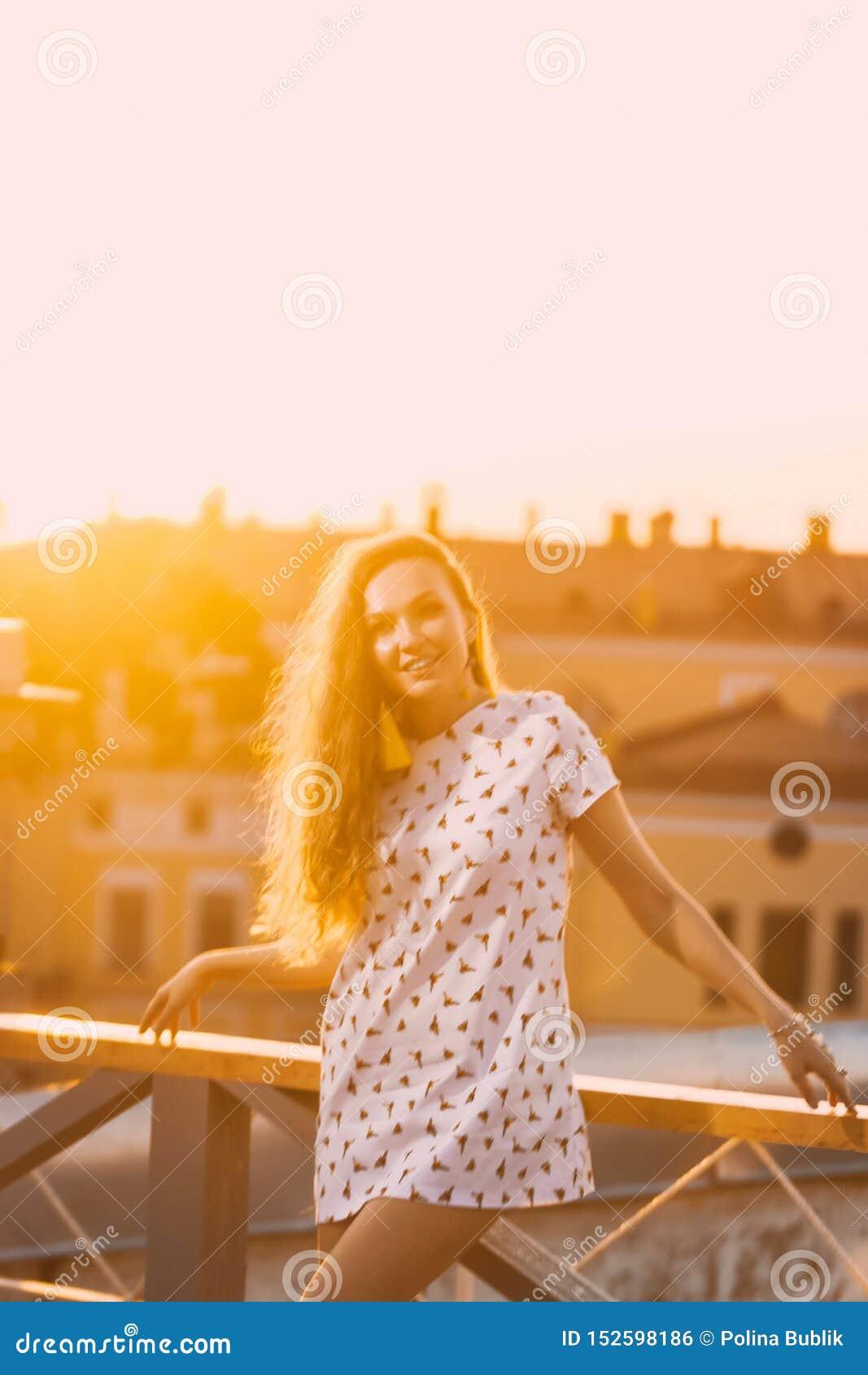 Retrato de los dientes atractivos jovenes hermosos de una sonrisa de la muchacha en un vestido corto blanco del verano en a de la