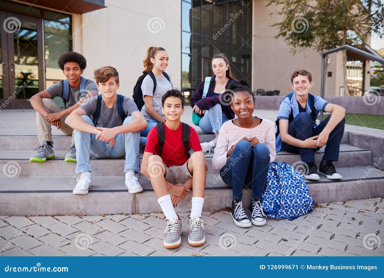 Retrato de los edificios de la universidad de Group Sitting Outside del estudiante de la High School secundaria
