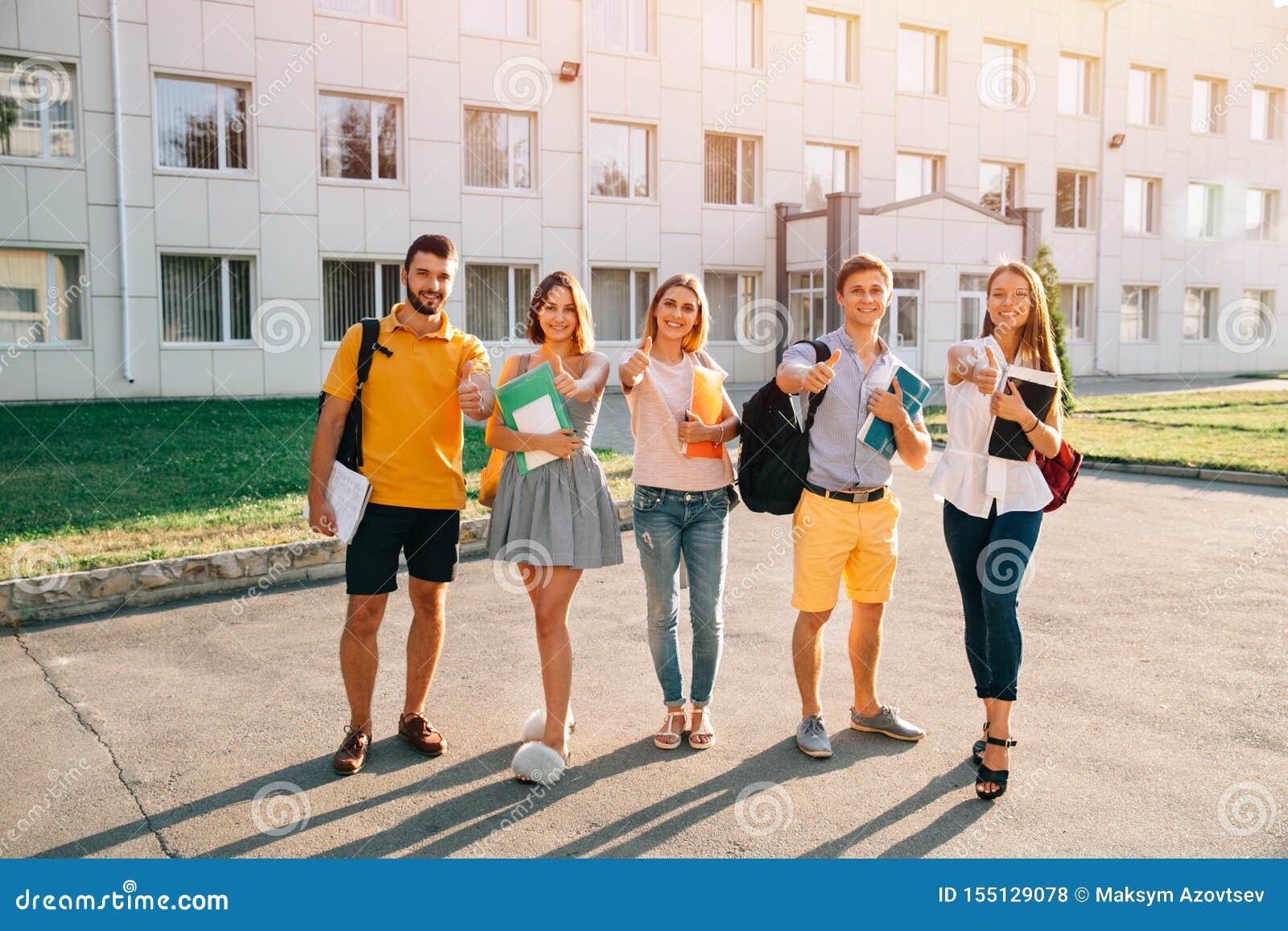 Retrato de los estudiantes del grupo en equipo casual con los libros que muestran los pulgares para arriba