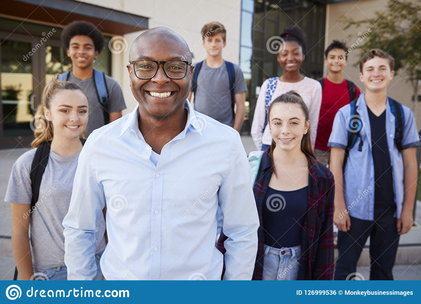 Retrato de los estudiantes de la High School secundaria con el profesor Outside College Buildings