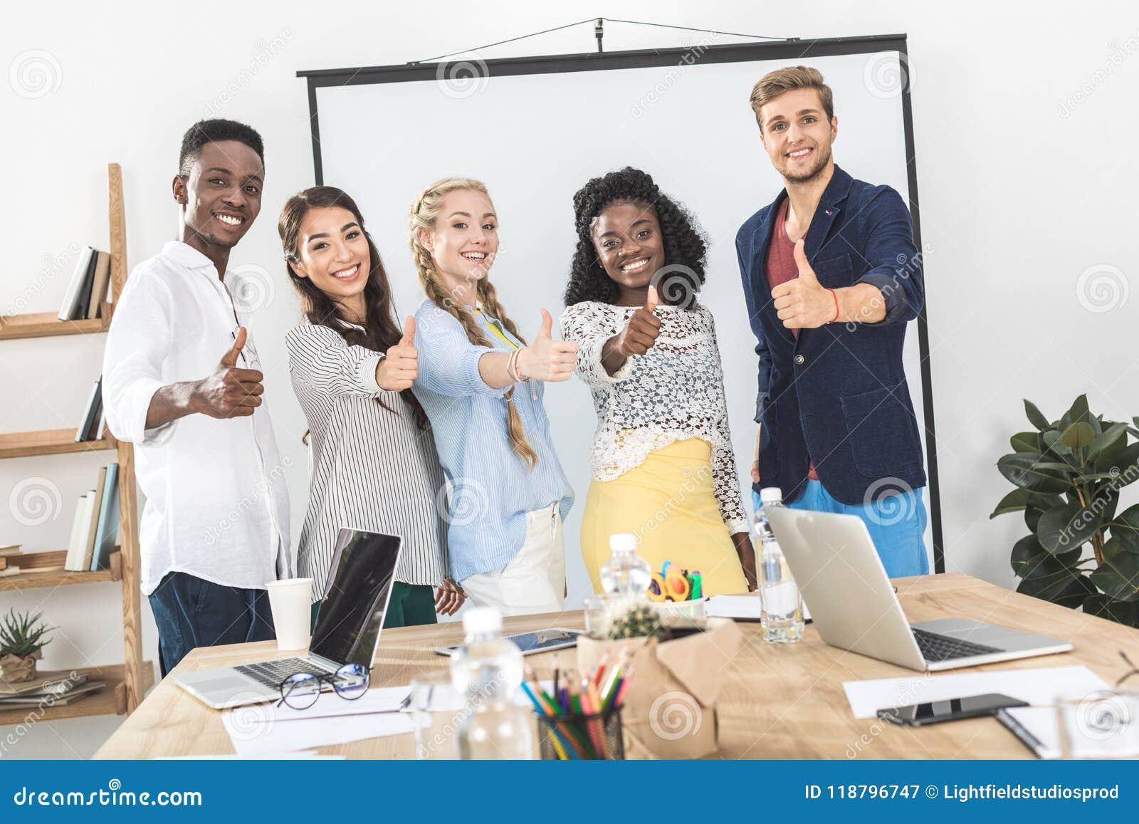 Retrato de los hombres de negocios sonrientes multiétnicos que muestran los pulgares para arriba