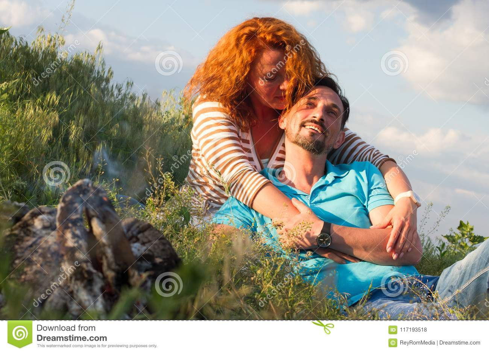 Retrato de los pares felices que ponen en la manta en hierba cerca de la chimenea en fondo de las nubes