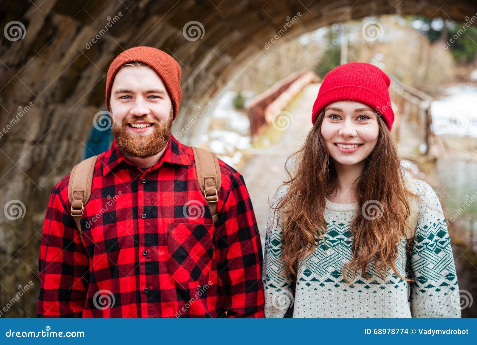 Retrato de los pares felices que se colocan al aire libre en invierno
