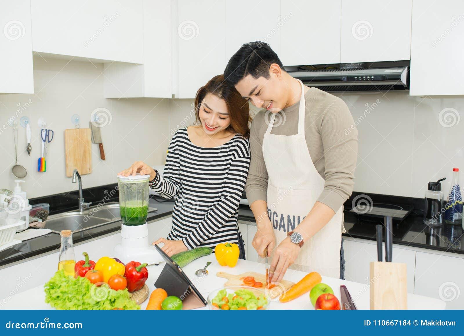 Retrato de los pares jovenes asiáticos felices que cocinan junto en el equipo