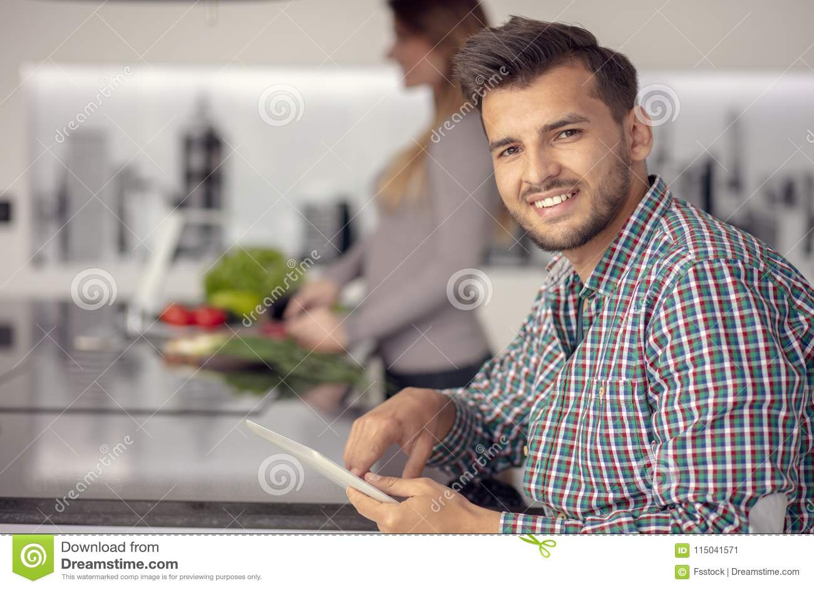 Retrato de los pares jovenes felices que cocinan junto en la cocina en casa