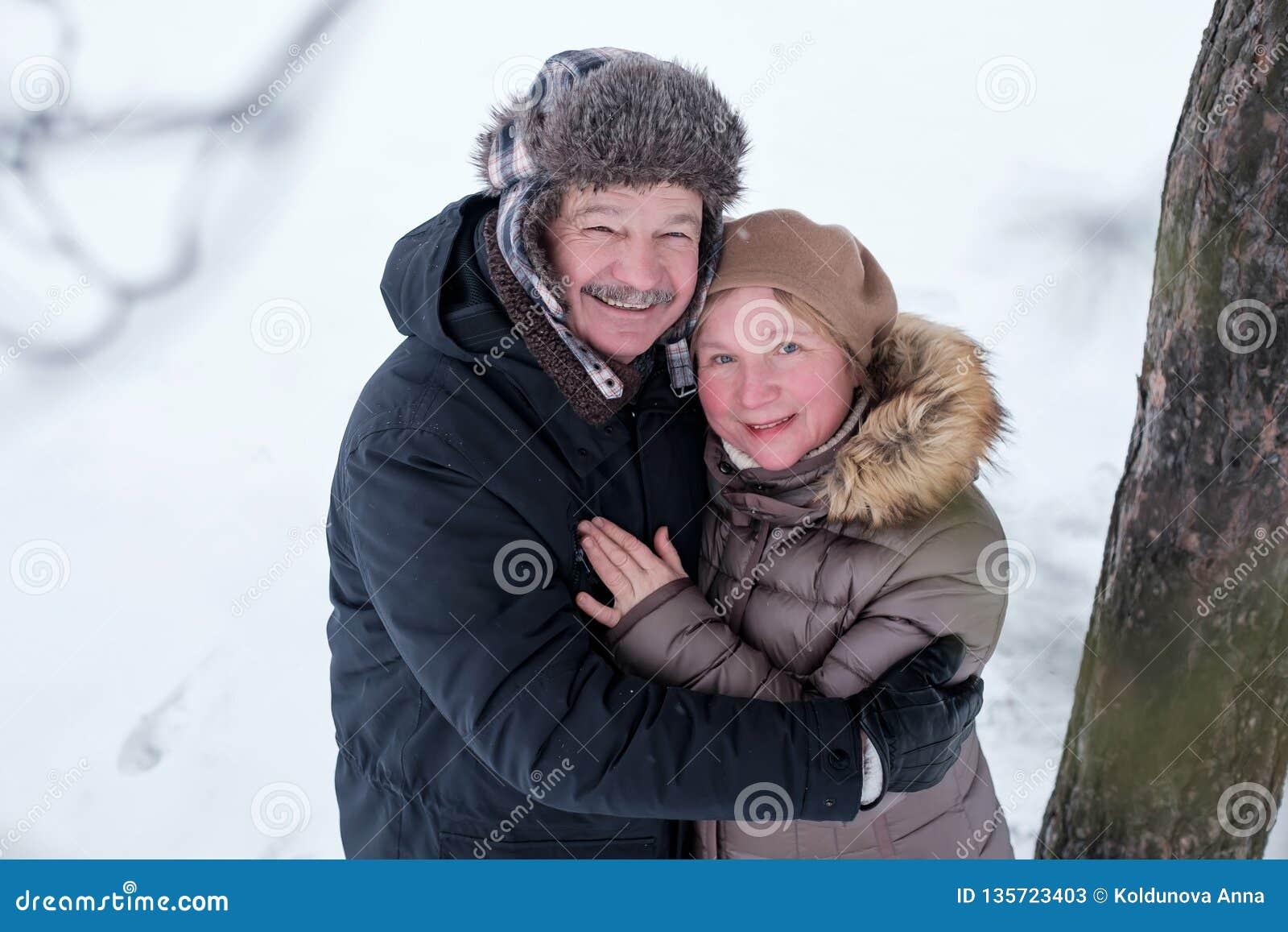 Retrato de los pares mayores que se divierten al aire libre en bosque del invierno