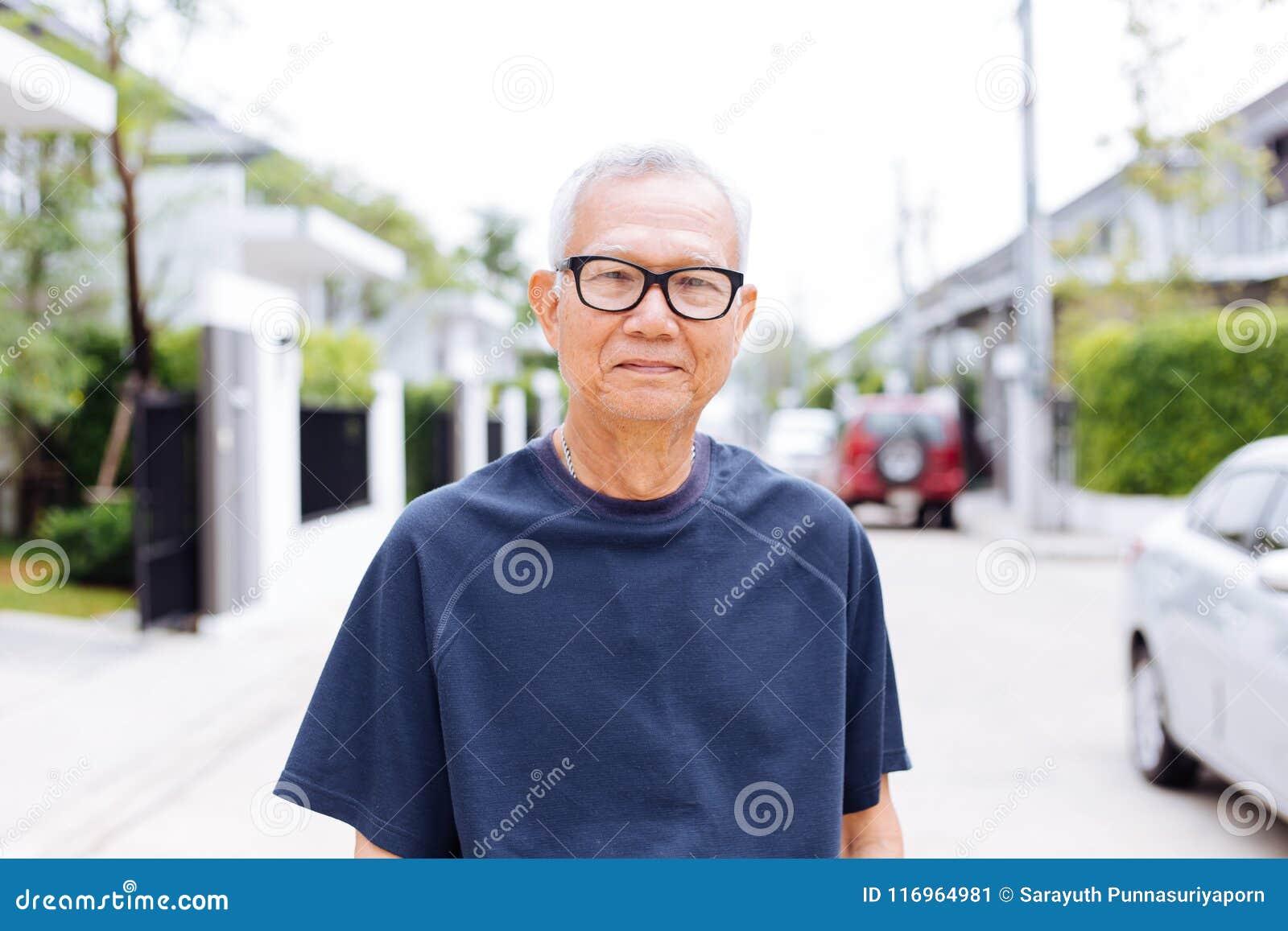 Retrato de los vidrios que llevan asiáticos y de mirar del hombre mayor la cámara en el distrito residencial con el coche y la ca
