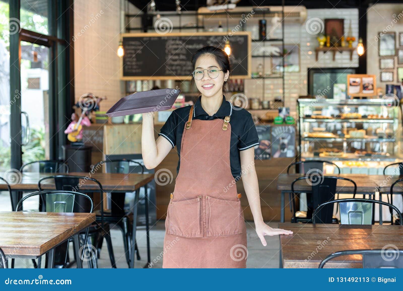 Retrato de los waiteress que sostienen la bandeja vacía en una cafetería