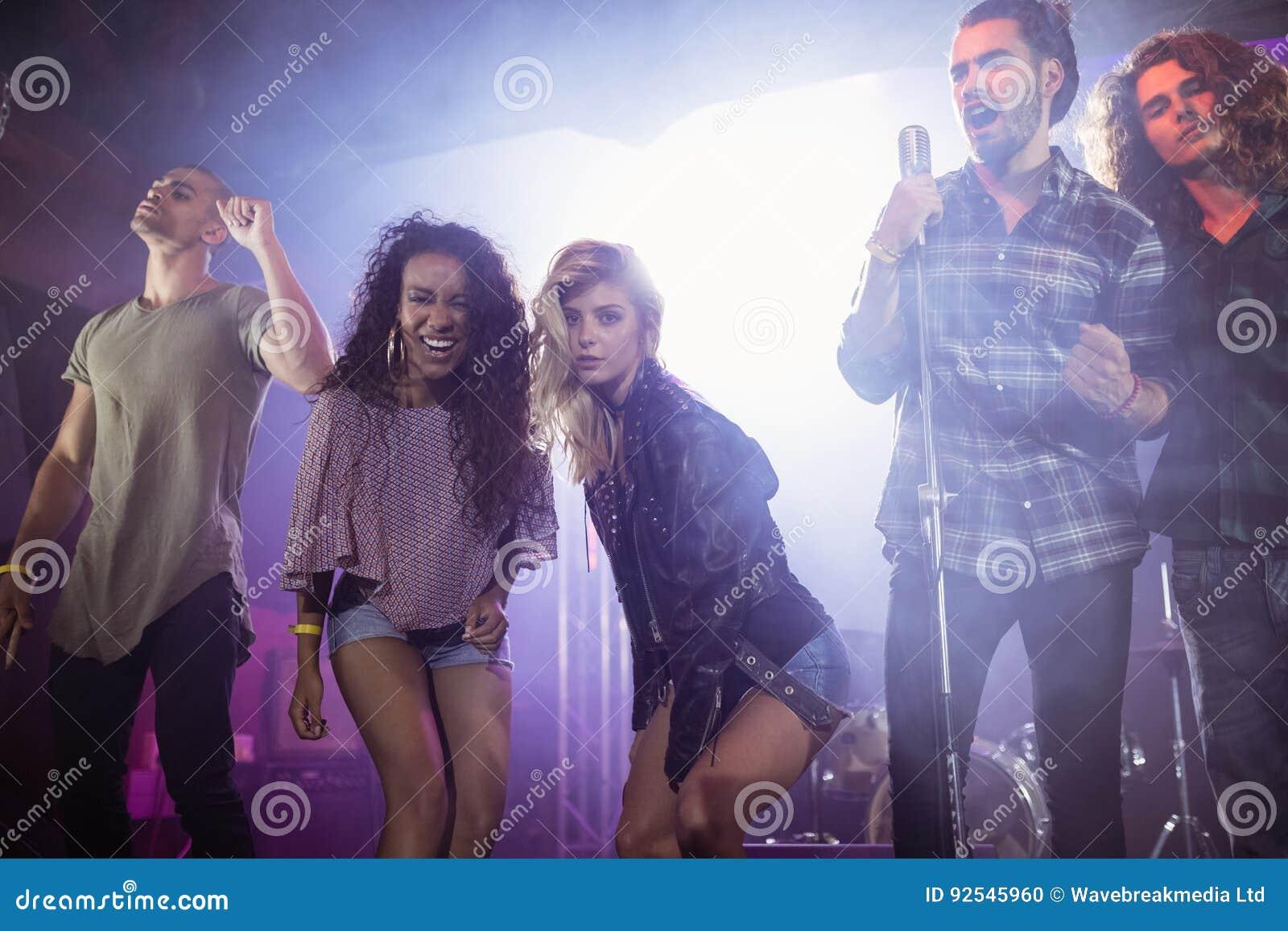 Retrato de músicos de sexo femenino con los ejecutantes masculinos en el club nocturno