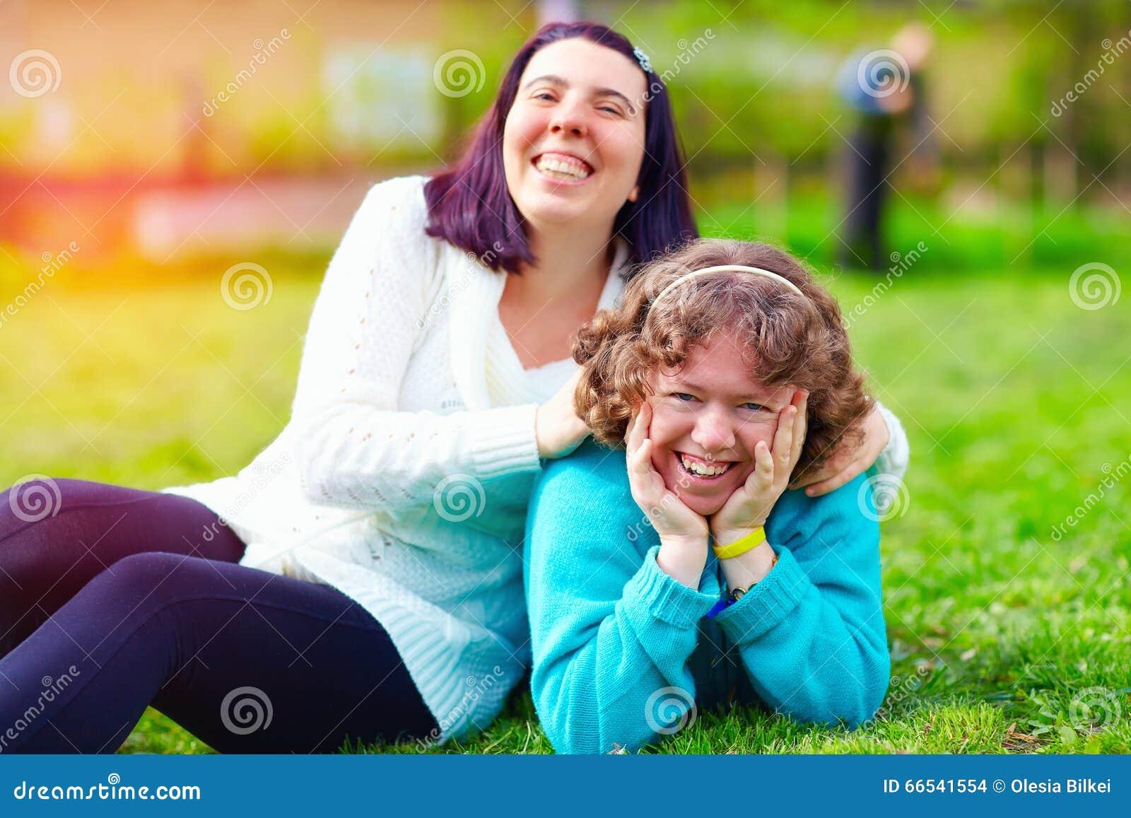 Retrato de mujeres felices con incapacidad en césped de la primavera