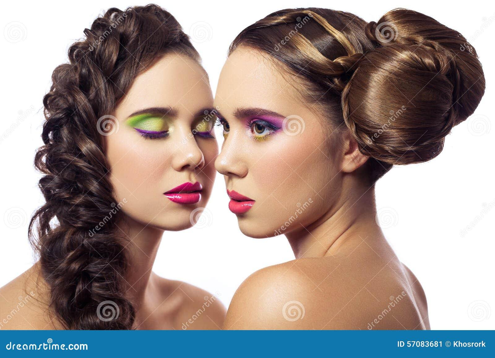 Retrato de mulheres novas da forma dos gêmeos bonitos com penteado e composição verde cor-de-rosa vermelha Isolado no fundo branc